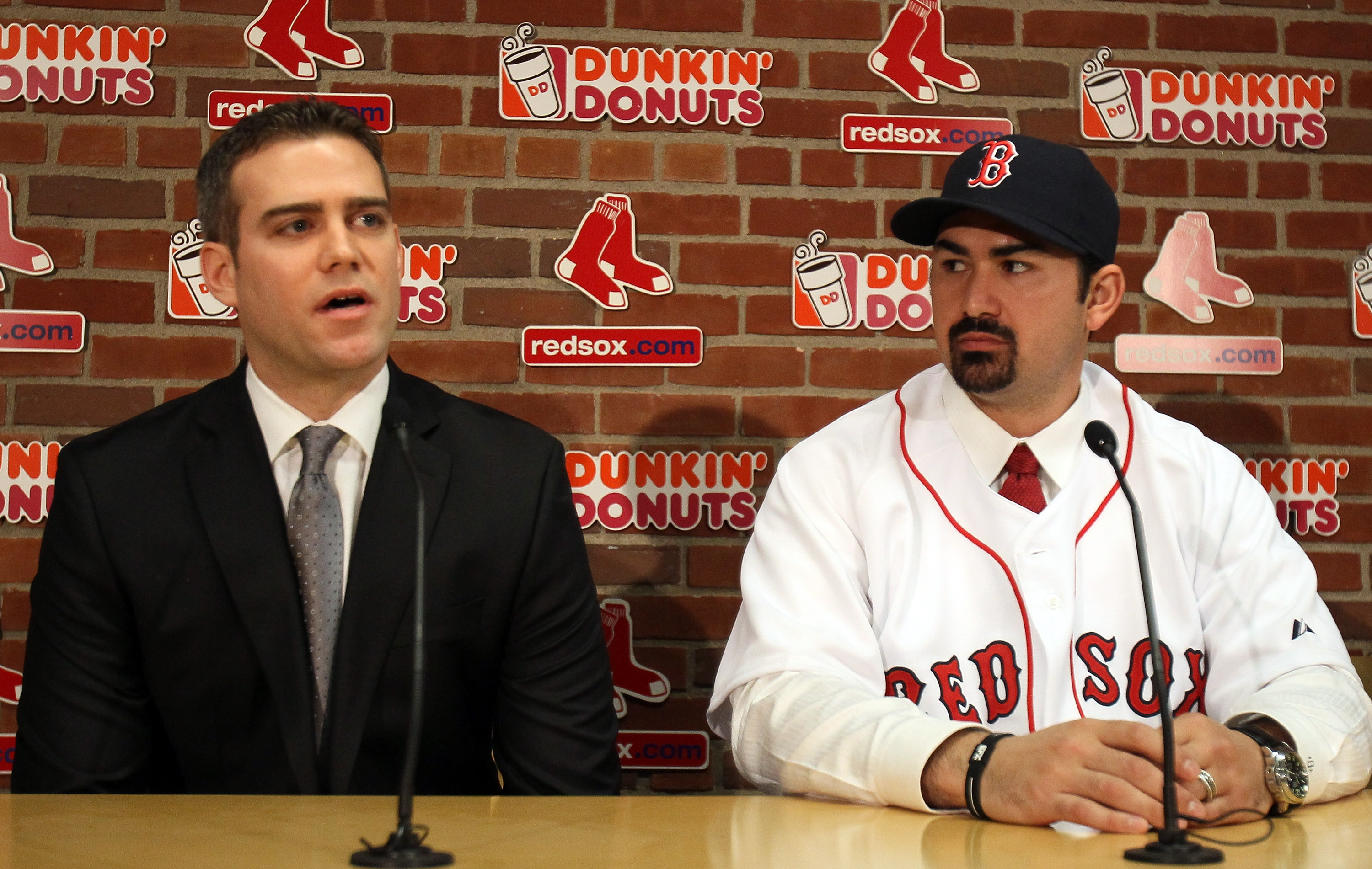 BOSTON, MA - DECEMBER 06:  Adrian Gonzalez (R) ooks on as General Manager Theo Epstein answers questions during a press conference to announce Gonzalez signing with the Boston Red Sox on December 6,  2010 at Fenway Park in Boston, Massachusetts.  (Photo b