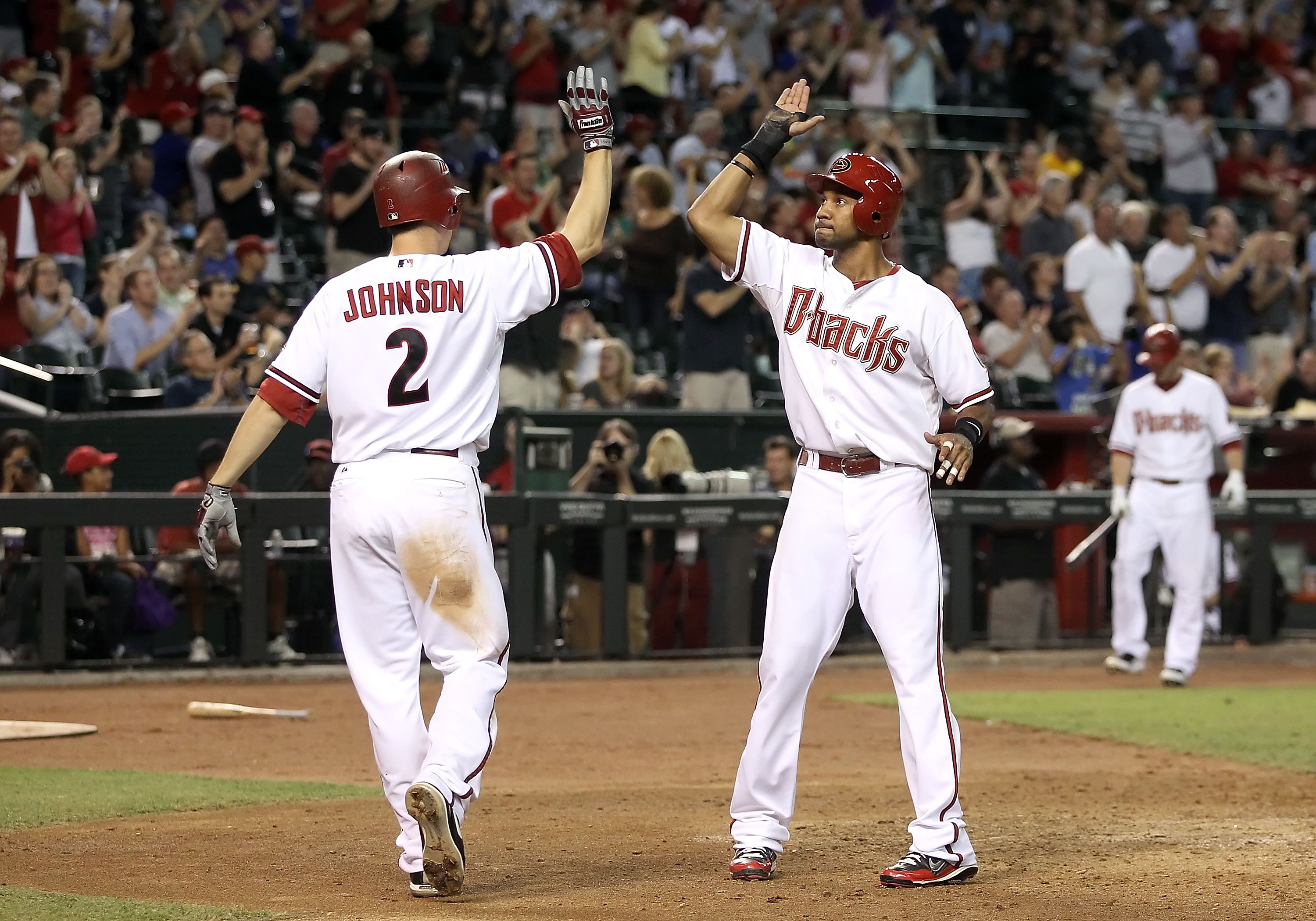PHOENIX - SEPTEMBER 24:  Chris Young #24 of the Arizona Diamondbacks is congratulated by teammate Kelly Johnson #2 after Young scored a ninth inning run against the Los Angeles Dodgers during the Major League Baseball game at Chase Field on September 24,