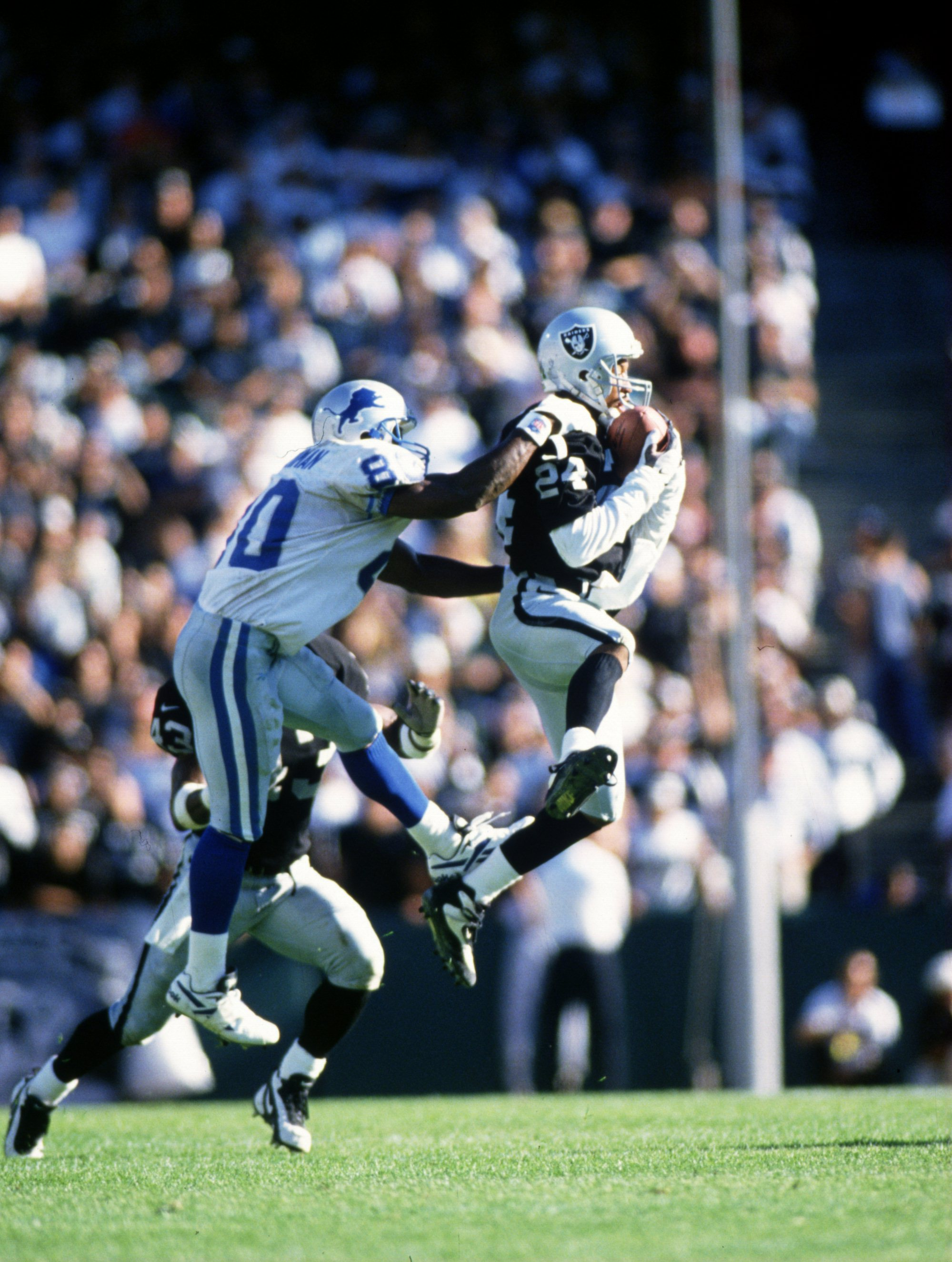 13 Oct 1996:  Defensive back Larry Brown #24 of the Oakland Raiders intercepts a pass thrown to wide receiver Brett Perriman #80 of the Detroit Lions during the Raiders 37-21 win at the Oakland Coliseum in Oakland, California. Mandatory Credit: Otto Greul