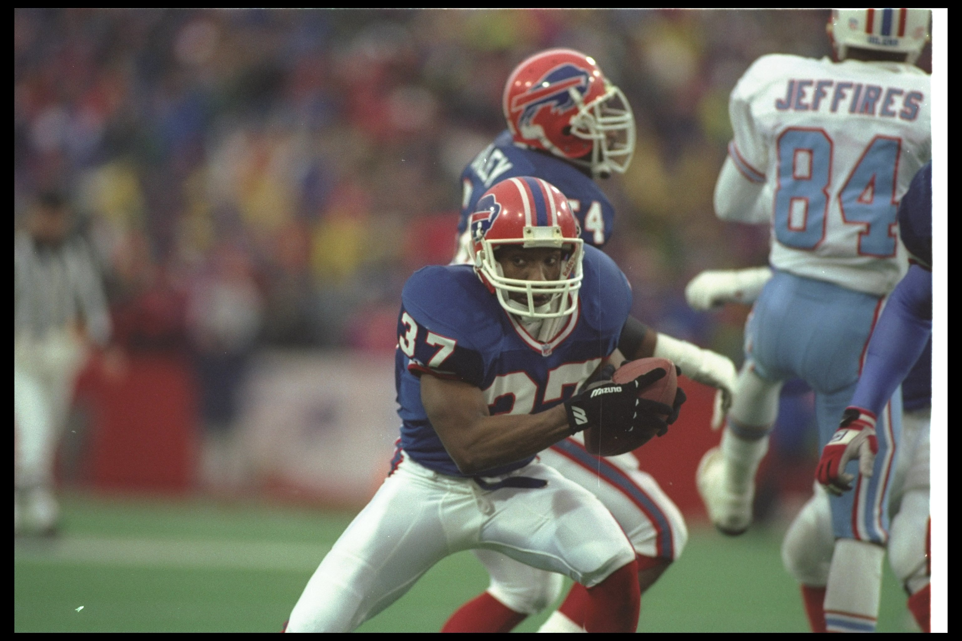 3 Jan 1993: Defensive back Nate Odomes of the Buffalo Bills runs with the ball after making an interception during a playoff game against the Houston Oilers at Rich Stadium in Orchard Park, New York. The Bills won the game in overtime, 41-38.