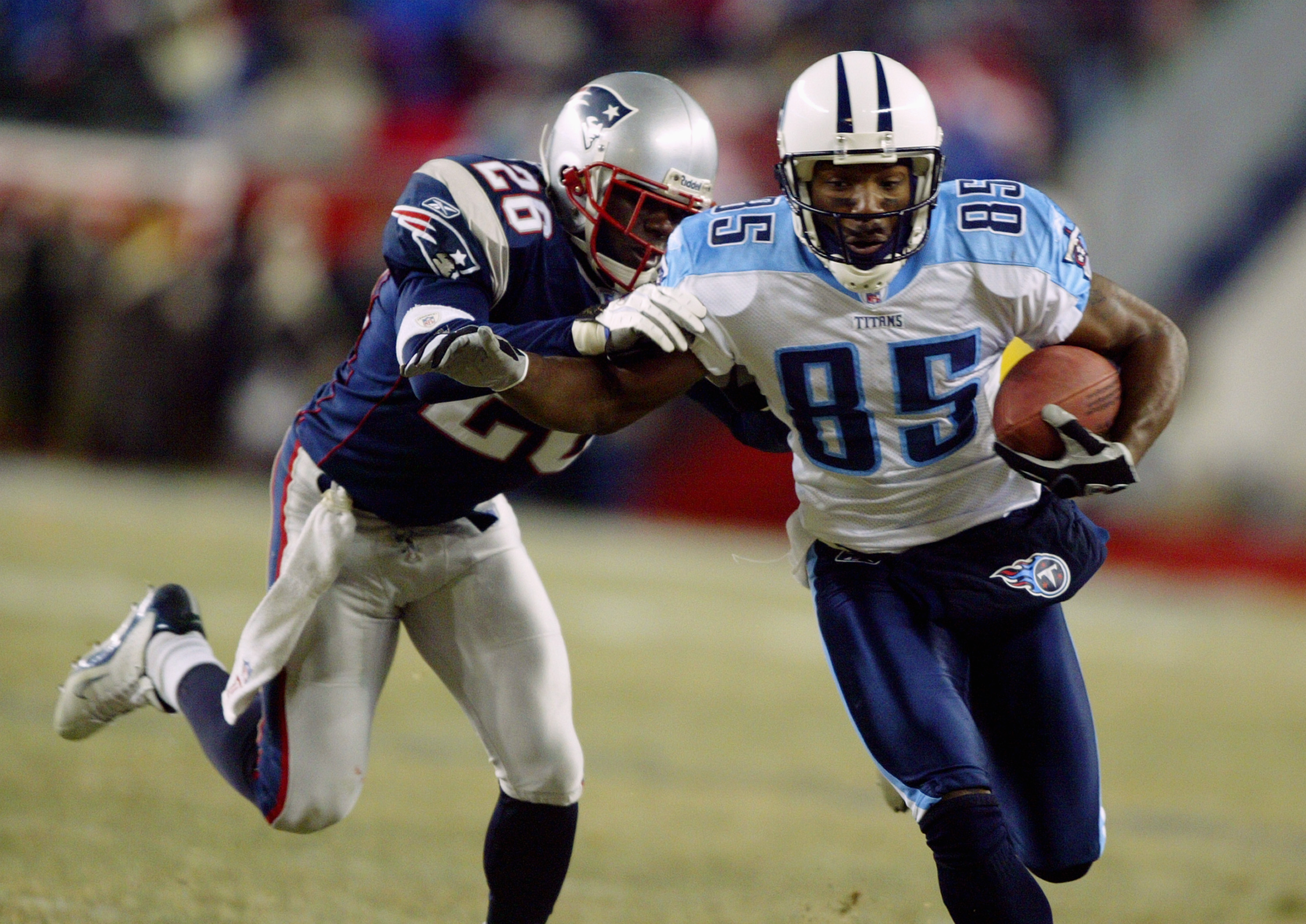 FOXBORO, MA - JANUARY 10:  Wide receiver Derrick Mason #85 of the Tennessee Titans tries to break a tackle by Eugene Wilson #85 of the New England Patriots in the AFC divisional playoffs on January 10, 2004 at Gillette Stadium in Foxboro, Massachusetts. T