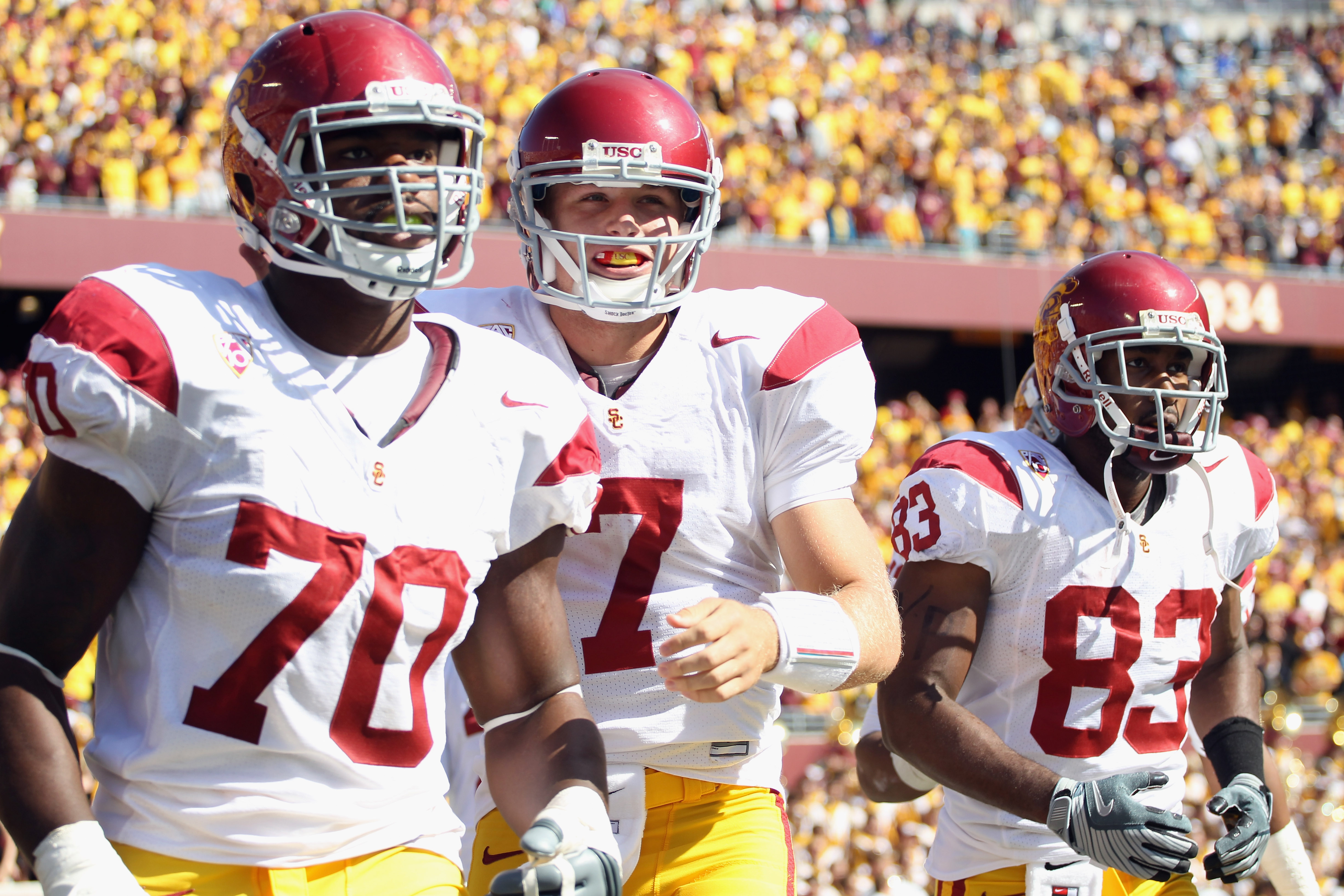 MINNEAPOLIS - SEPTEMBER 18:  Quarterback Matt Barkley #7 of the USC Trojans, flanked by Tyron Smith #70 and Ronald Johnson #83, runs off the field after the Trojans scored a touchdown during the first half of the game against the Minnesota Golden Gophers