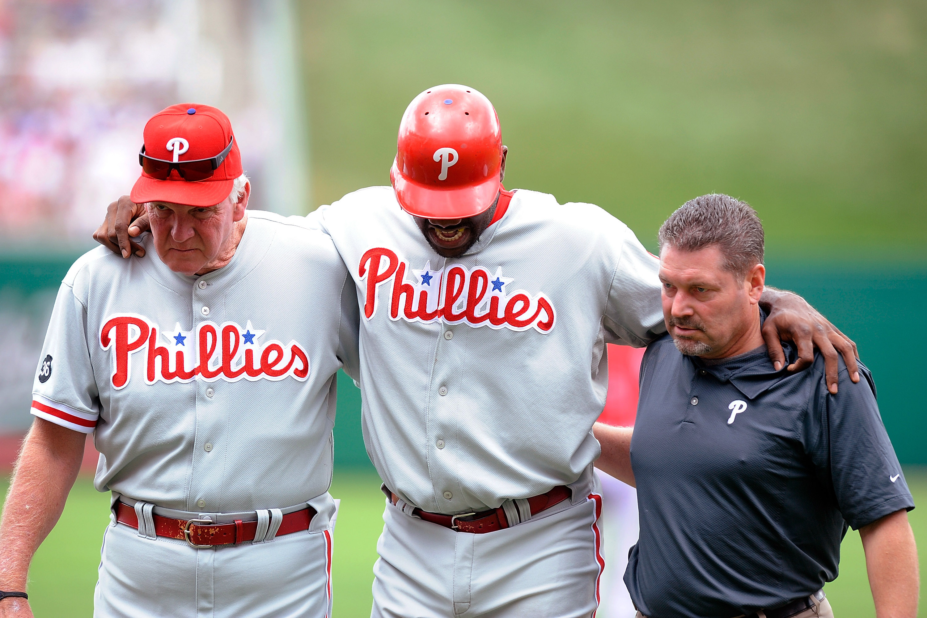 WASHINGTON - AUGUST 01:  Ryan Howard #6 of the Philadelphia Phillies is helped off the field by manager Charlie Manuel and a Philadelphia trainer after injuring his ankle during the first inning against the Washington Nationals at Nationals Park on August