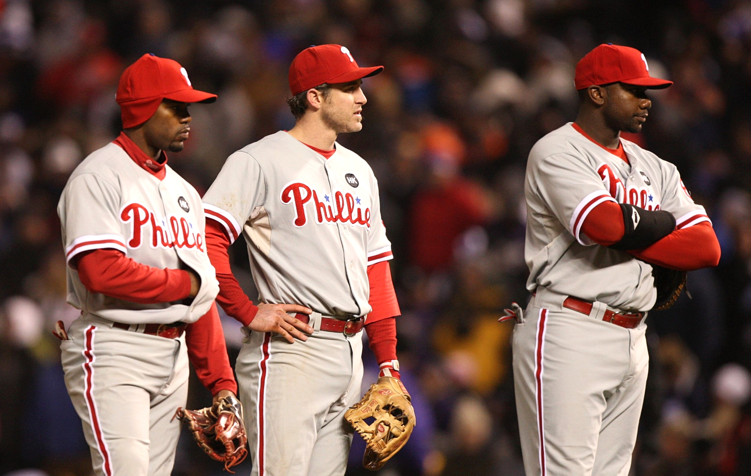DENVER - OCTOBER 11:  (L-R) Jimmy Rollins #11, Chase Utley #26 and Ryan Howard #6 of the Philadelphia Phillies wait for a pitching change after an injury to Scott Eyre (not pictured) against the Colorado Rockies in Game Three of the NLDS during the 2009 M