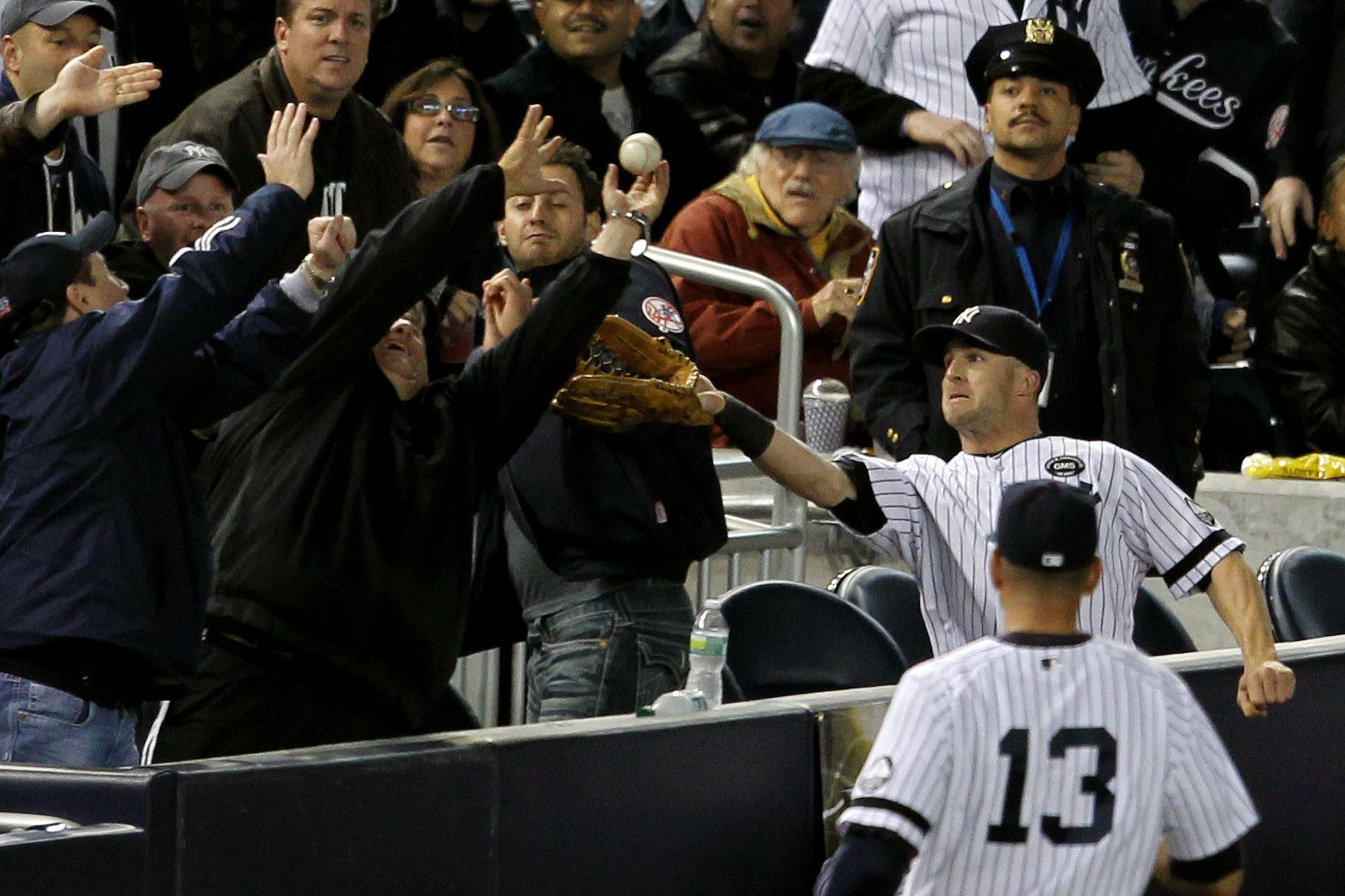 NEW YORK - OCTOBER 19:  Brett Gardner #11 of the New York Yankees tries to make a play in foul territory as a fan gets in the way against the Texas Rangers in Game Four of the ALCS during the 2010 MLB Playoffs at Yankee Stadium on October 19, 2010 in the