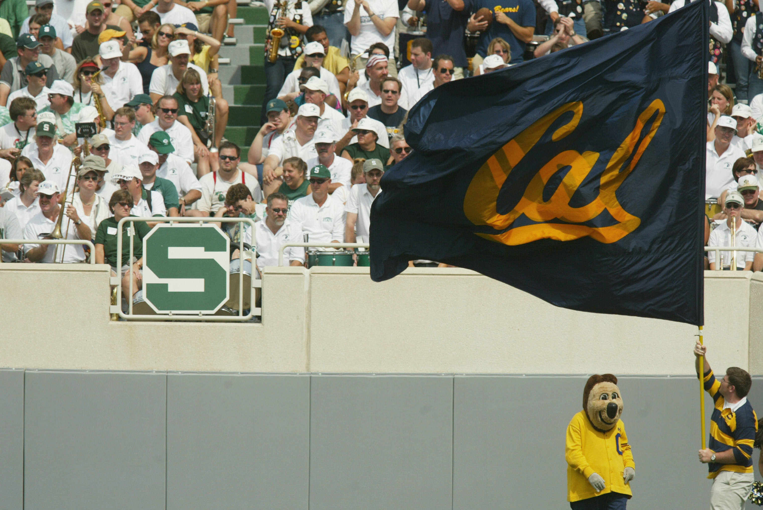 EAST LANSING, MI - SEPTEMBER 14:  A member of the California Golden Bears spirit squad waves a team flag while standing next to the Bears' mascot in front of the Michigan State Spartans crowd on September 14, 2002 at Spartan Stadium in East Lansing, Michi