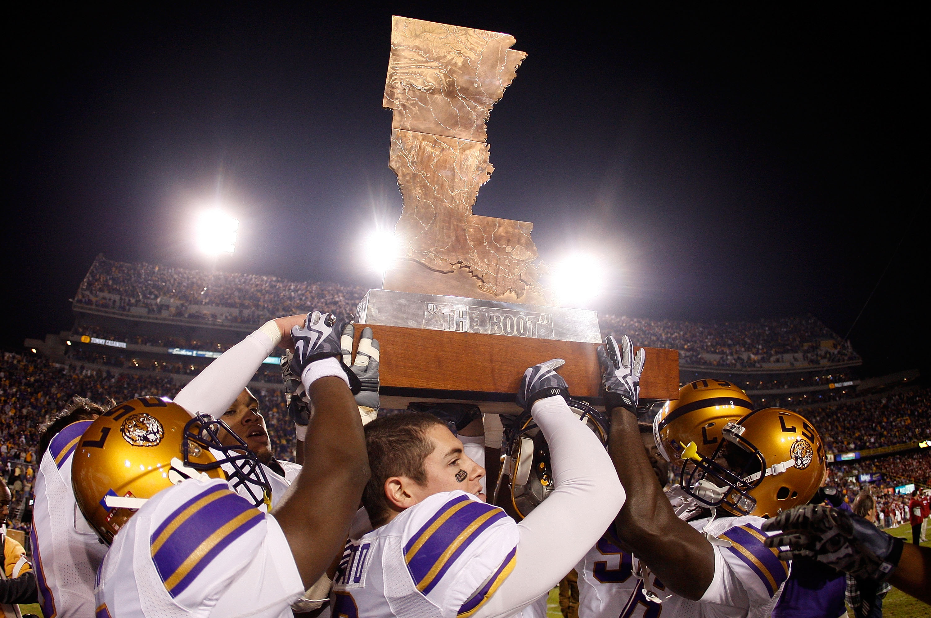 BATON ROUGE, LA - NOVEMBER 28:  Members of the LSU Tigers celebrate with 'The Boot' trophy after defeating the Arkansas Razorbacks 33-30 in overtime at Tiger Stadium on November 28, 2009 in Baton Rouge, Louisiana.  (Photo by Chris Graythen/Getty Images)
