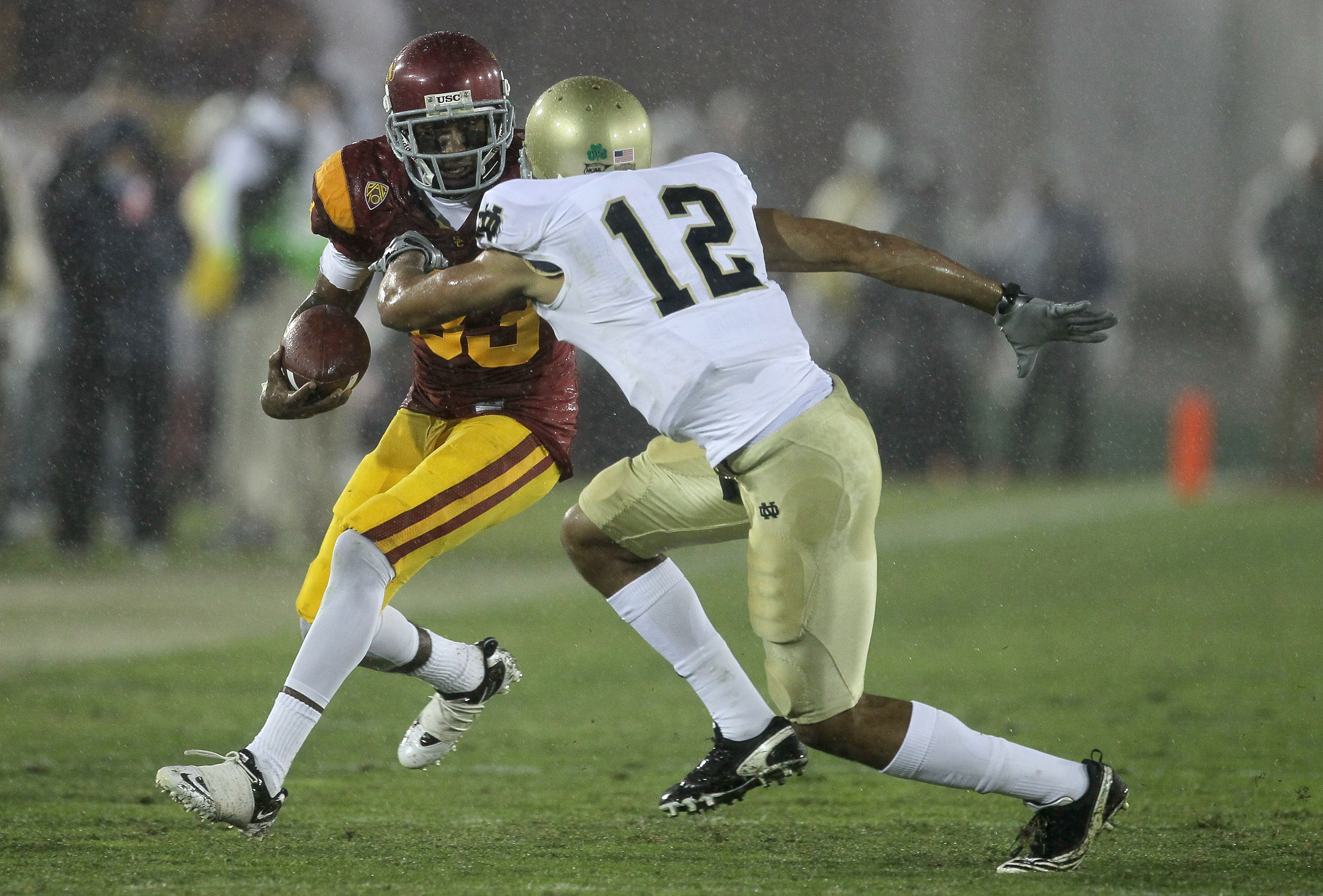 LOS ANGELES, CA - NOVEMBER 27:  Wide receiver Ronald Johsnon #83 of the USC Trojans carries the ball against cornerback Robert Blanton #12 of the Notre Dame Fighting Irish at the Los Angeles Memorial Coliseum on November 27, 2010 in Los Angeles, Californi