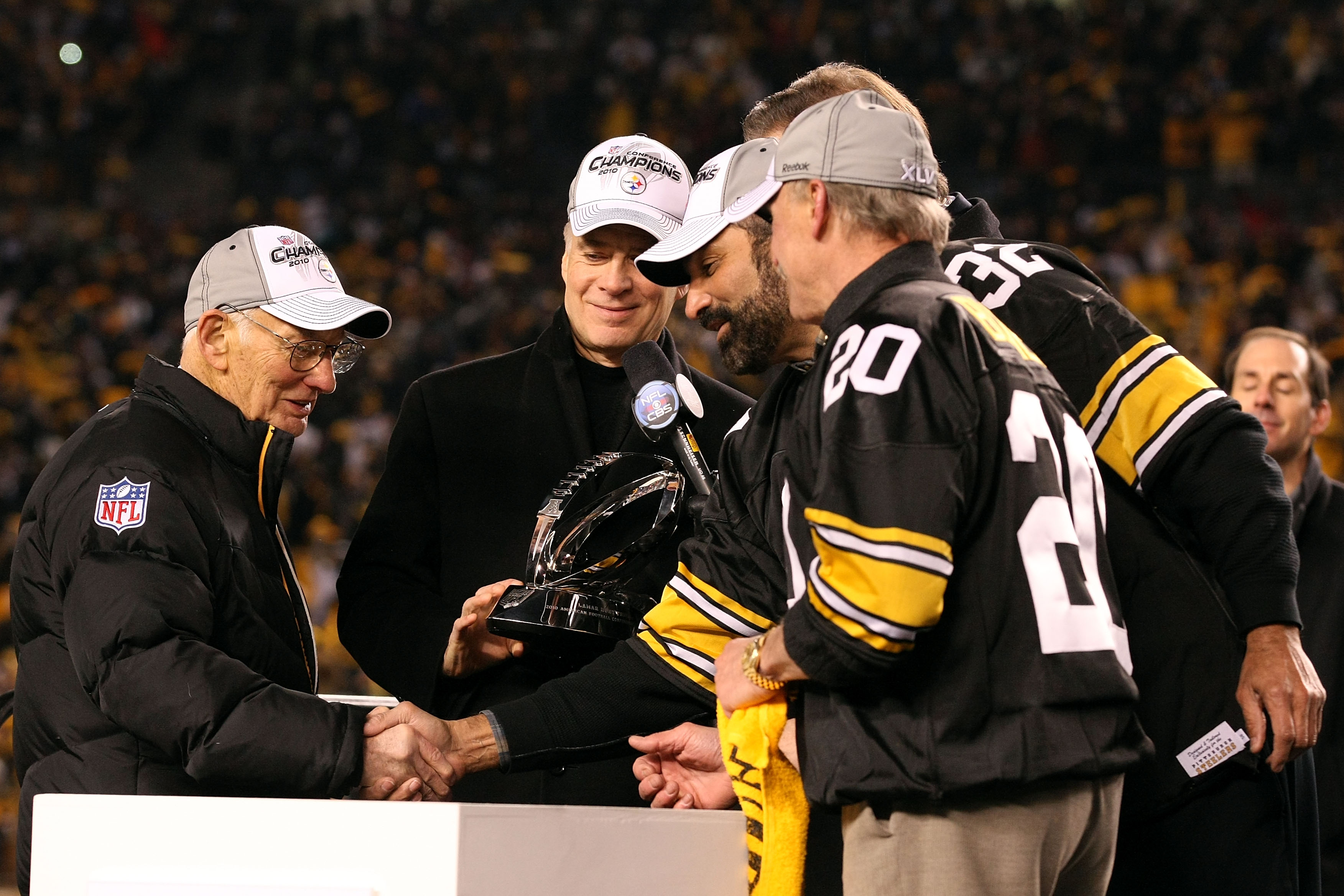 PITTSBURGH, PA - JANUARY 23:  Owner Dan Rooney (L) and Team president Art Rooney II (2ndL) of the Pittsburgh Steelers recieve the Lamar Hunt Trophy from former Steelers' players Franco Harris and Rocky Bleier (R) after their 24 to 19 win over the New York