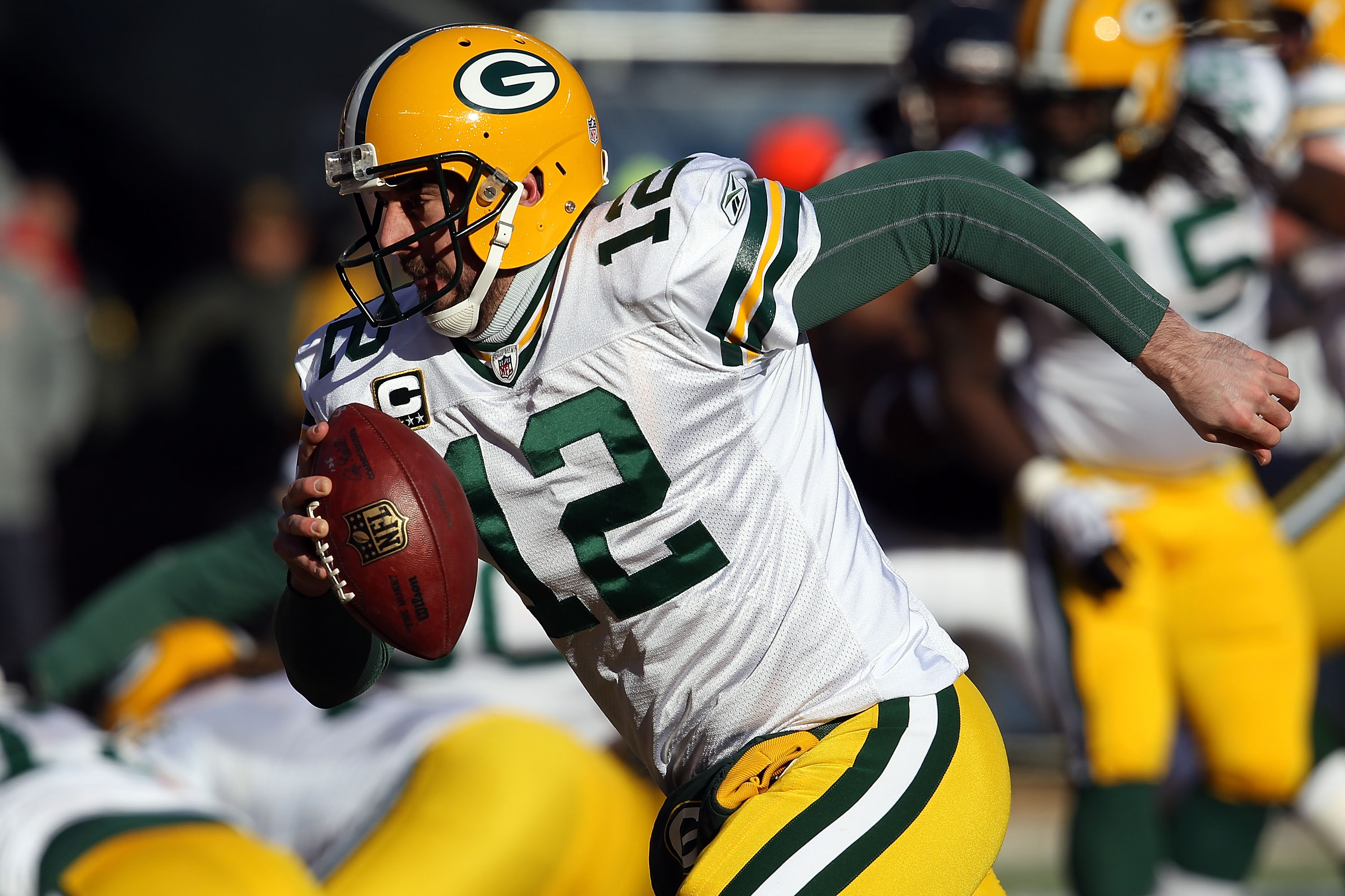 CHICAGO, IL - JANUARY 23:  Quarterback Aaron Rodgers #12 of the Green Bay Packers runs the ball to the corner of the endzone for a one-yard touchdown run against Danieal Manning #38 of the Chicago Bears in the first quarter of the NFC Championship Game at