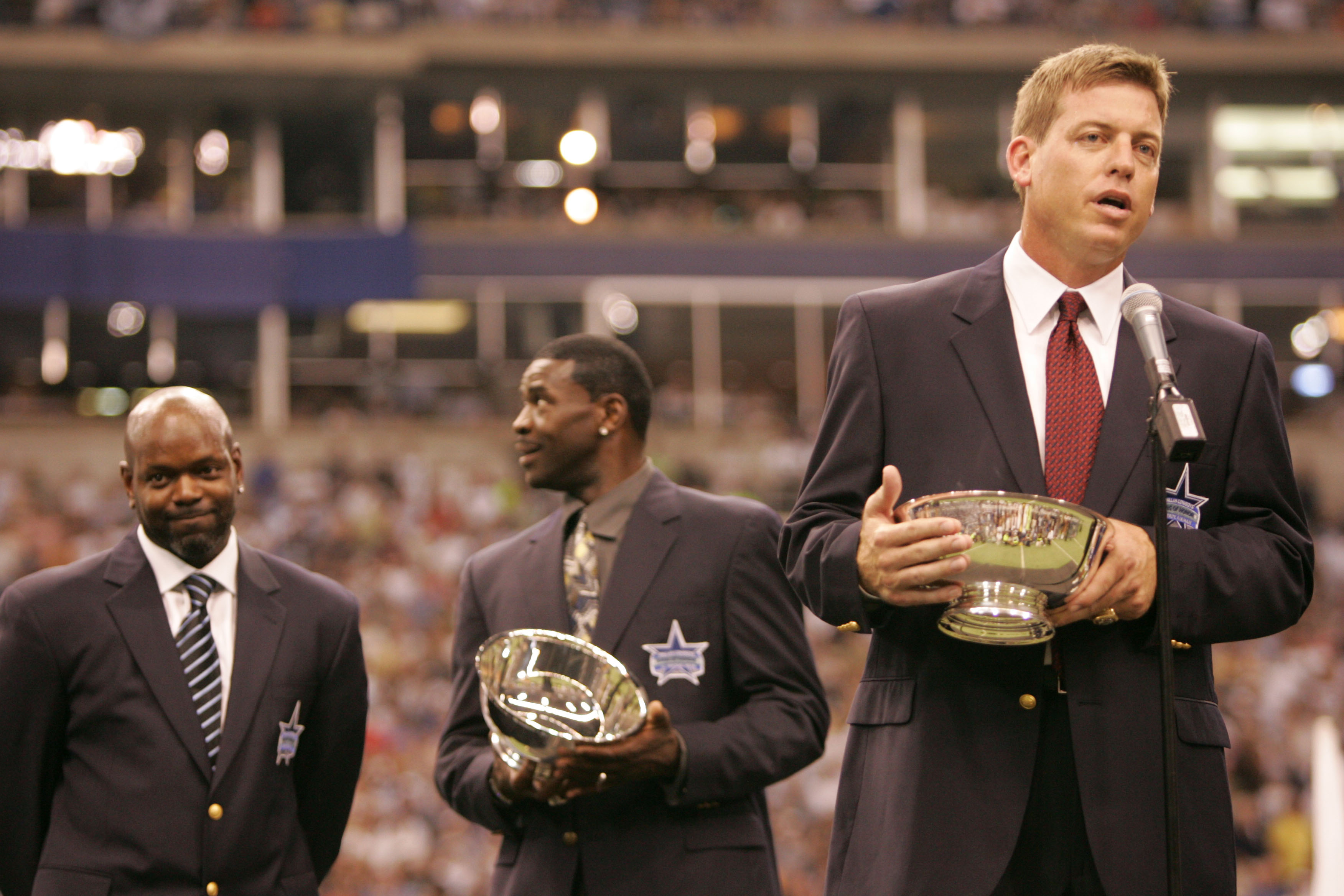 IRVING, TX - SEPTEMBER 19:  Troy Aikman, former Dallas Cowboys quaterback, speaks to the fans in front of former teammates Emmitt Smith (L) and Michael Irvin during a ceremony inducting Aikman into the Cowbos ring of honor at half-time of the game between