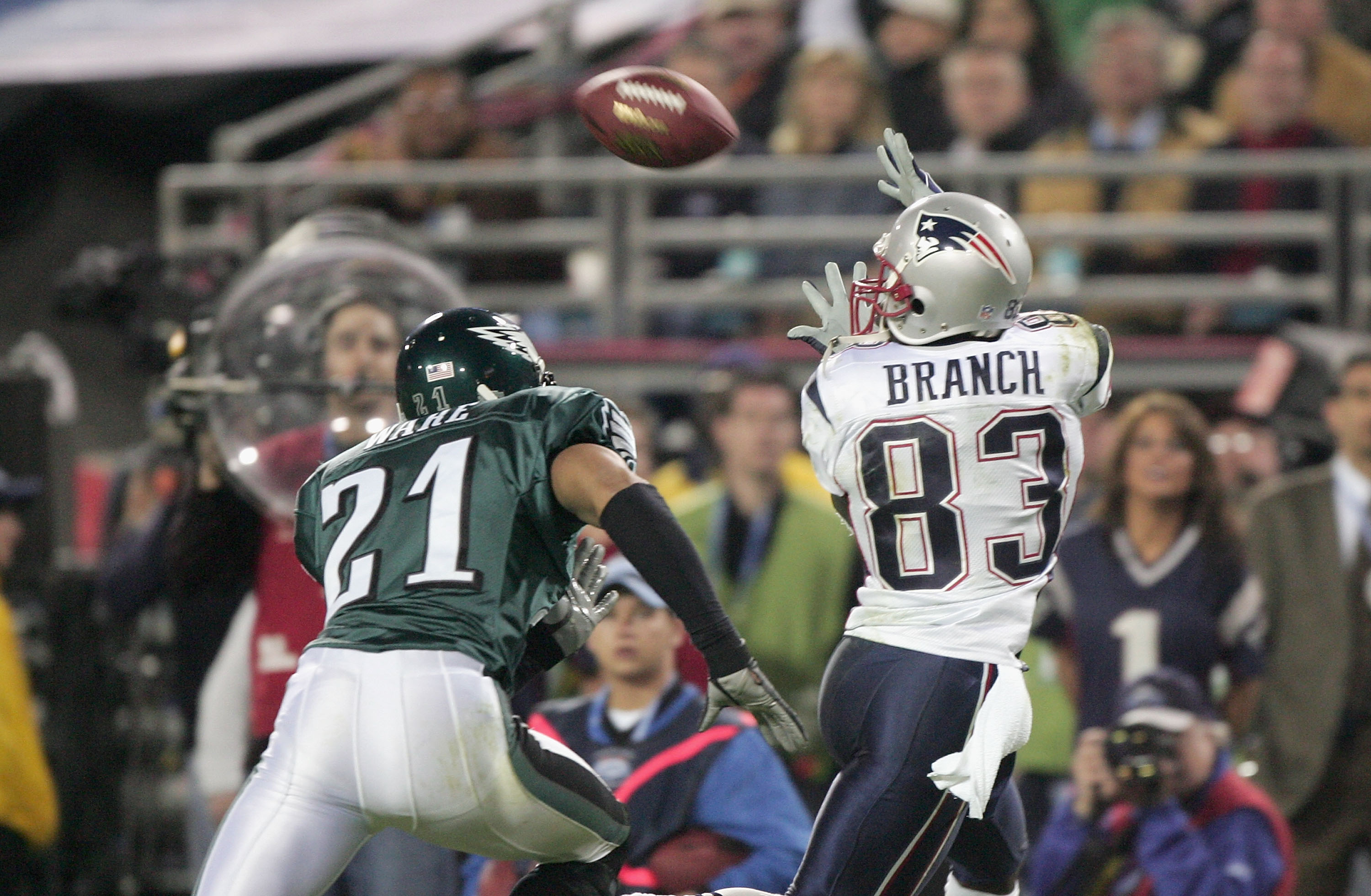 JACKSONVILLE, FL - FEBRUARY 6:  Wide receiver Deion Branch #83 of the New England Patriots receives a pass over Matt Ware #21 of the Philadelphia Eagles during Super Bowl XXXIX at Alltel Stadium on February 6, 2005 in Jacksonville, Florida. The Patriots d