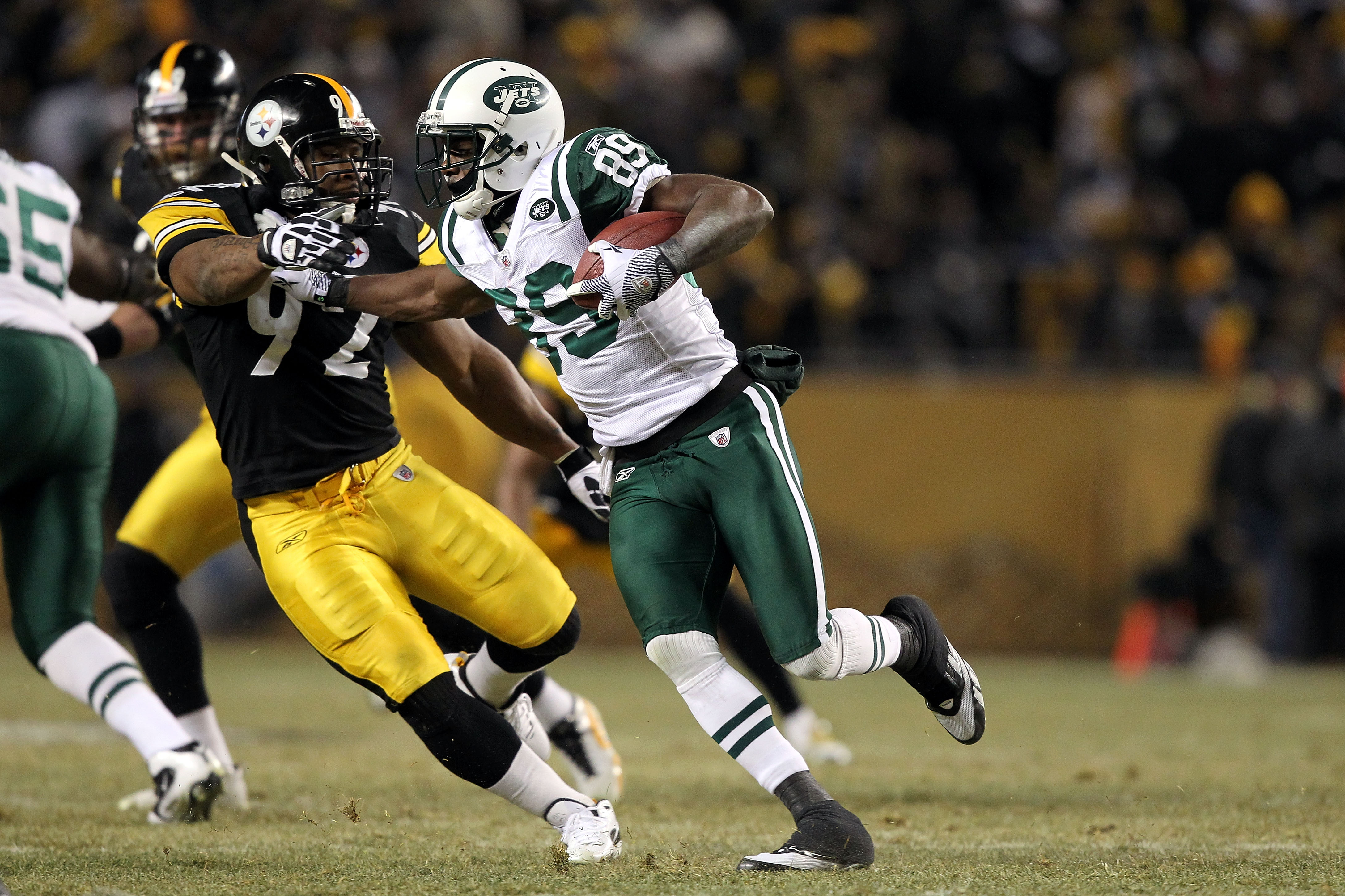 PITTSBURGH, PA - JANUARY 23:  Jerricho Cotchery #89 of the New York Jets runs with the ball against James Harrison #92 of the Pittsburgh Steelers during the 2011 AFC Championship game at Heinz Field on January 23, 2011 in Pittsburgh, Pennsylvania. The Ste
