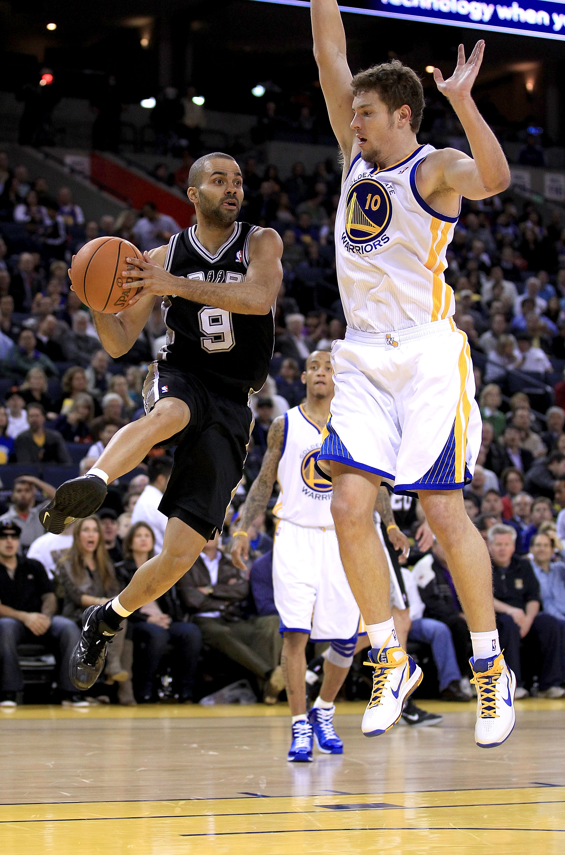 OAKLAND, CA - JANUARY 24:  Tony Parker #9 of the San Antonio Spurs drives on David Lee #10 of the Golden State Warriors at Oracle Arena on January 24, 2011 in Oakland, California.  NOTE TO USER: User expressly acknowledges and agrees that, by downloading