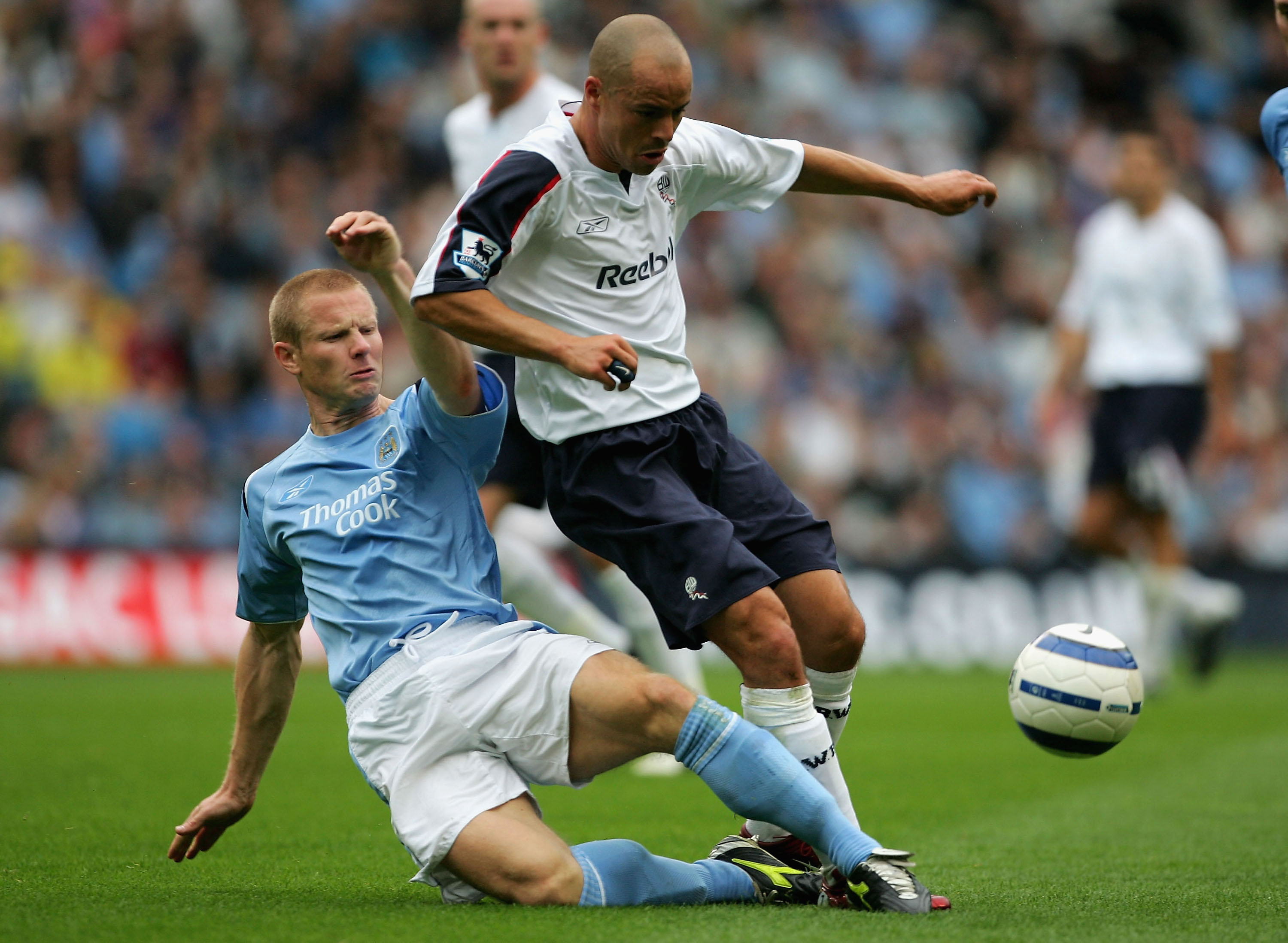 MANCHESTER, ENGLAND - SEPTEMBER 18:  Ben Thatcher of Manchester City tackles Stelios Giannakopoulos of Bolton Wanderers during the Barclays Premiership match between Manchester City and Bolton Wanderers at the City of Manchester Stadium on September 18, 2