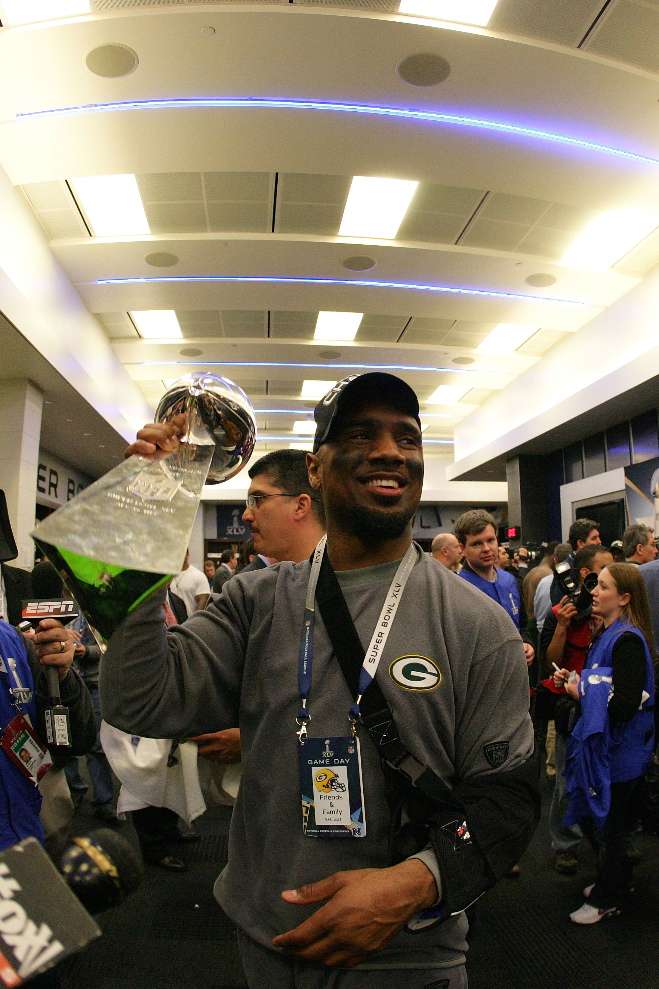 ARLINGTON, TX - FEBRUARY 06: Charles Woodson #21 of the Green Bay Packers celebrates in the locker room with the Vince Lombardi Trophy after winning Super Bowl XLV 31-25 against the Pittsburgh Steelers at Cowboys Stadium on February 6, 2011 in Arlington,
