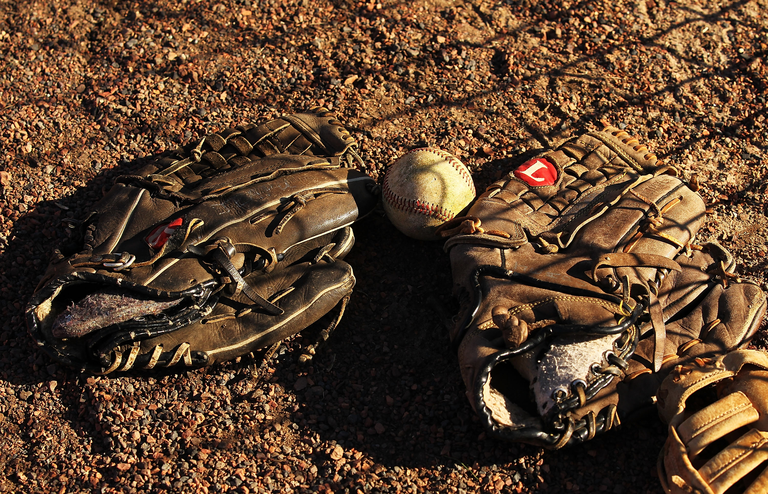 KISSIMMEE, FL - JANUARY 28:  Baseball gloves and a baseball lie in the dirt during the Jim Evans Academy of Professional Umpiring on January 28, 2011 at the Houston Astros Spring Training Complex  in Kissimmee, Florida.  Jim Evans was a Major League Umpir