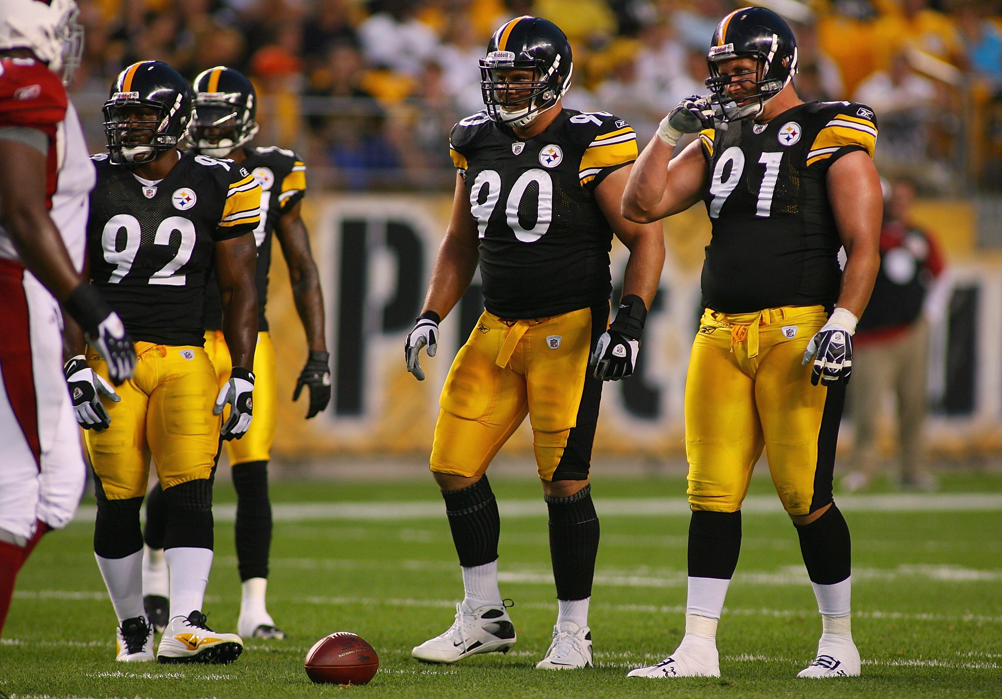 PITTSBURGH - AUGUST 13:  (L-R) James Harrison #92, Travis Kirschke #90, and Aaron Smith #91 of the Pittsburgh Steelers stand at the line of scrimmage during the preseason NFL game against the Arizona Cardinals at Heinz Field on August 13, 2009 in Pittsbur
