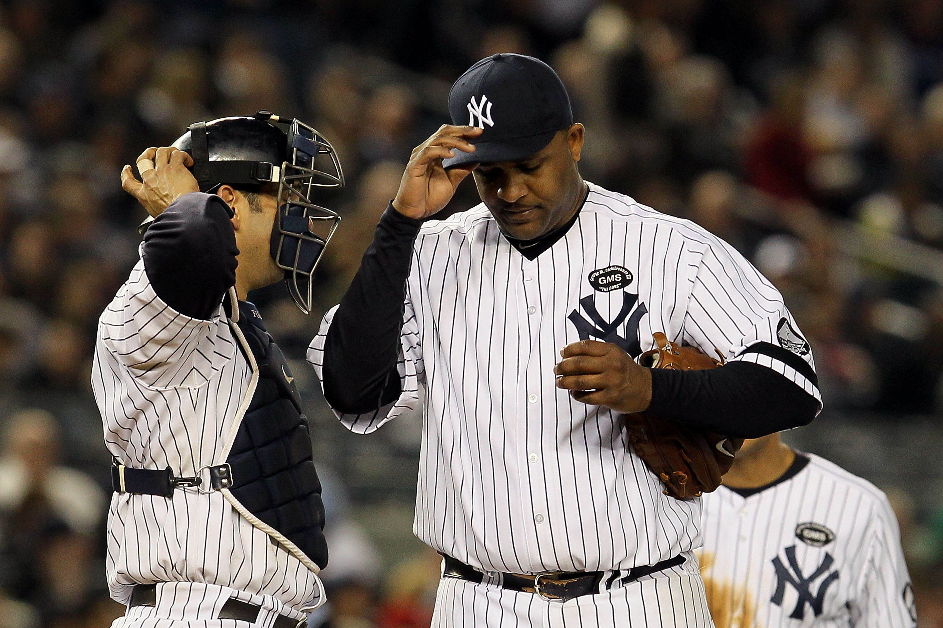 NEW YORK - OCTOBER 20:  Starting pitcher CC Sabathia #52 of the New York Yankees adjusts his cap as he talks with catcher Jorge Posada #20 after Sabathia gave up a single to Jeff Francoeur #21 of the Texas Rangers to load the bases in the top of the sixth