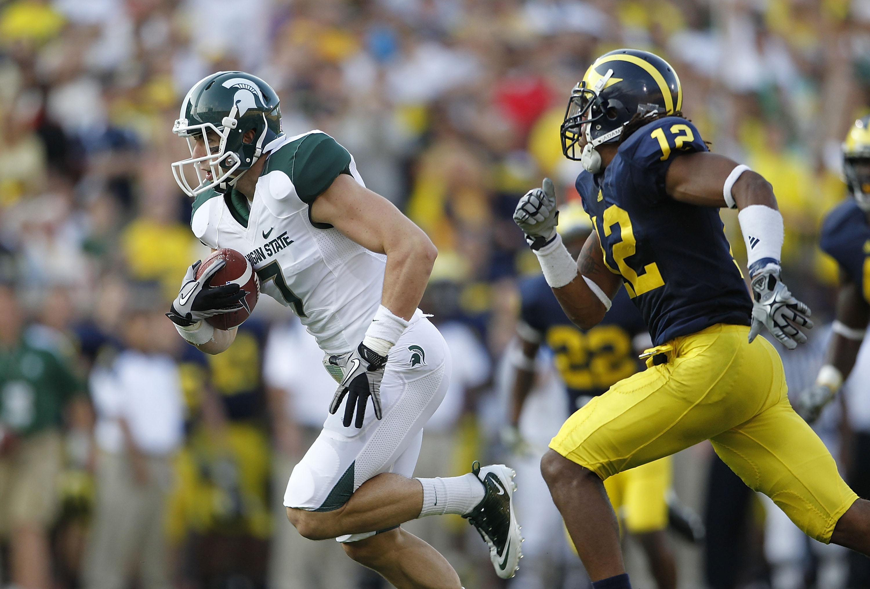 ANN ARBOR, MI - OCTOBER 09:  Steve Nichol #7 of the Michigan State Spartans runs past J. T. Floyd #12 of the Michigan Wolverines after catching a 42 yard pass compleation from Kirk Cousins #8 during the third quarter of the game against the Michigan Wolve