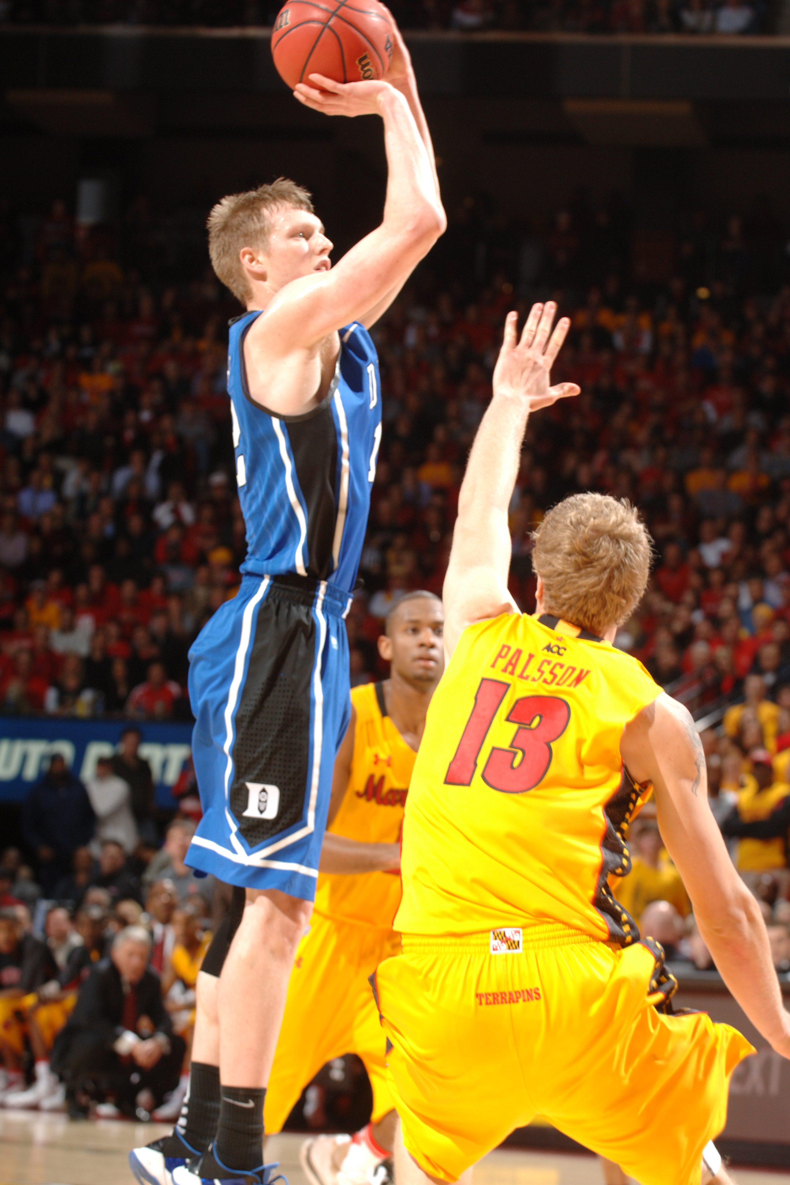 COLLEGE PARK, MD - FEBRUARY 2: Kyle Singler #12 of the Duke Blue Devils takes a jump shot over Haukur Paulsson #13 of the Maryland terrapins during a college basketball game on February 2, 2011 at the Comcast Arena in College Park, Maryland. The Blue Devi