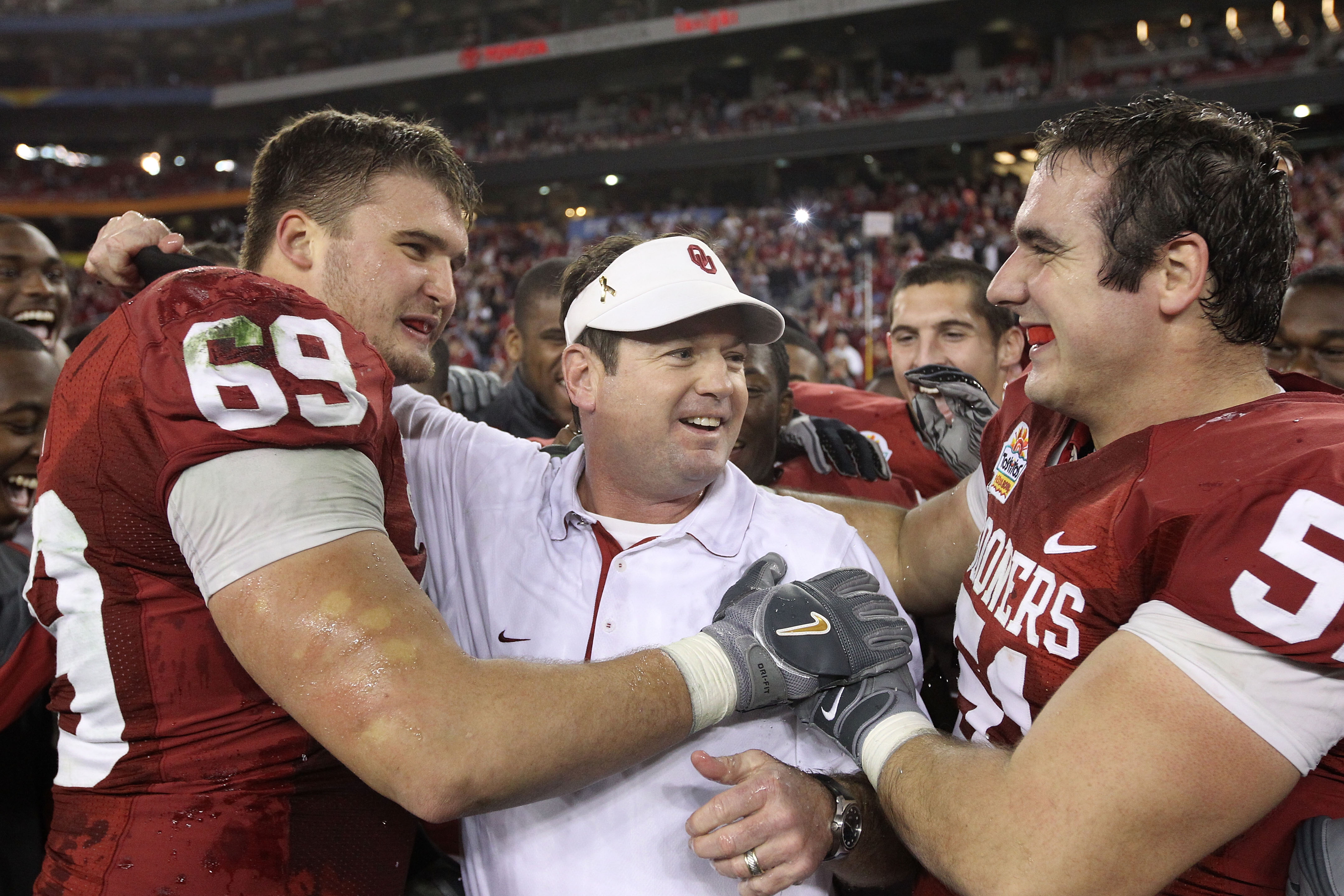 GLENDALE, AZ - JANUARY 01:  Head coach Bob Stoops is hugged by Eric Mensik #69 and Brian Lepak #51 late in the fourth quarter before the Sooners 48-20 victory against the Connecticut Huskies during the Tostitos Fiesta Bowl at the Universtity of Phoenix St
