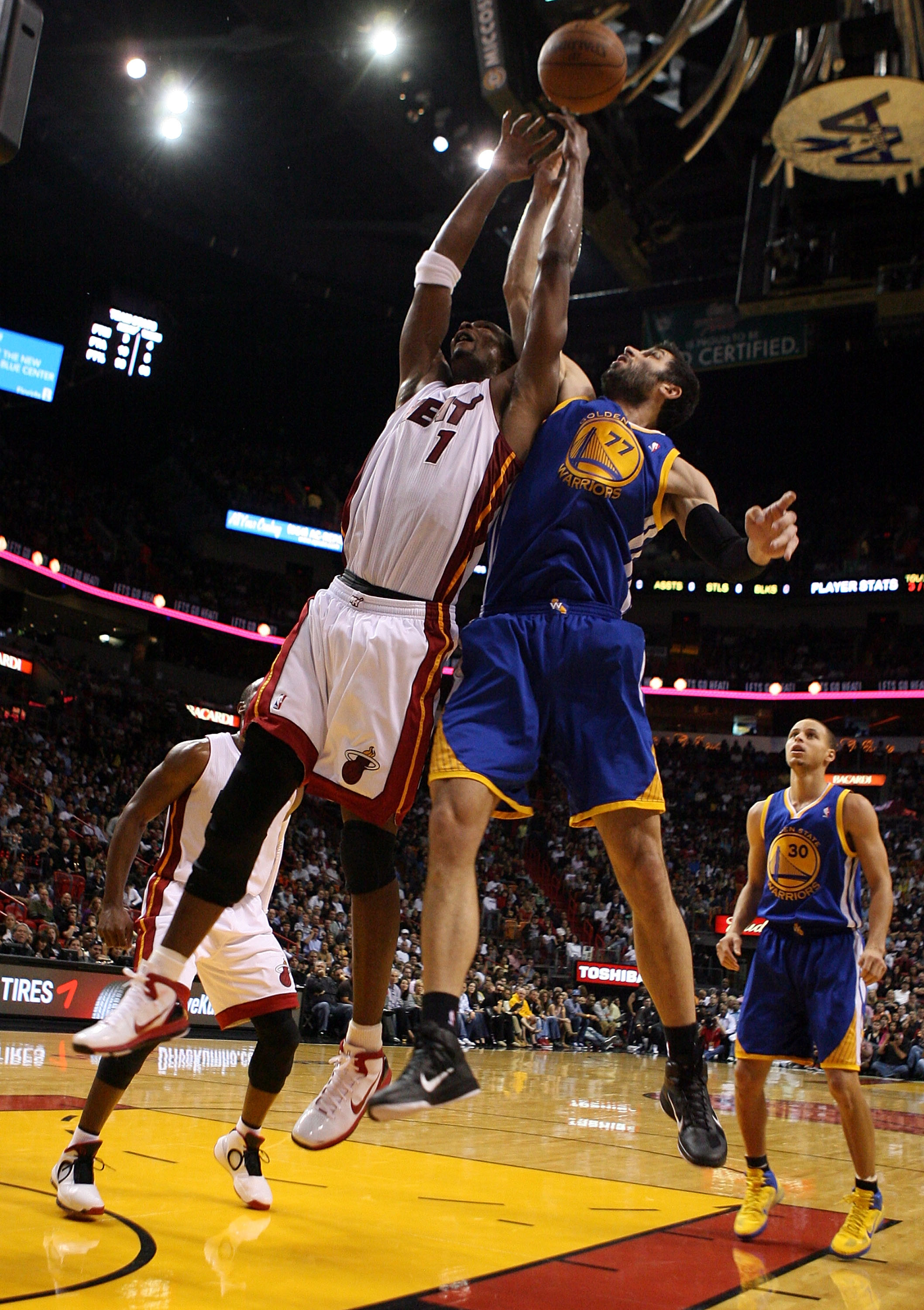 MIAMI, FL - JANUARY 01:  Forward Chris Bosh #1 of the Miami Heat rebounds over forward Vladimir Radmanovic #77 of the Golden State Warriors at American Airlines Arena on January 1, 2011 in Miami, Florida.  NOTE TO USER: User expressly acknowledges and agr