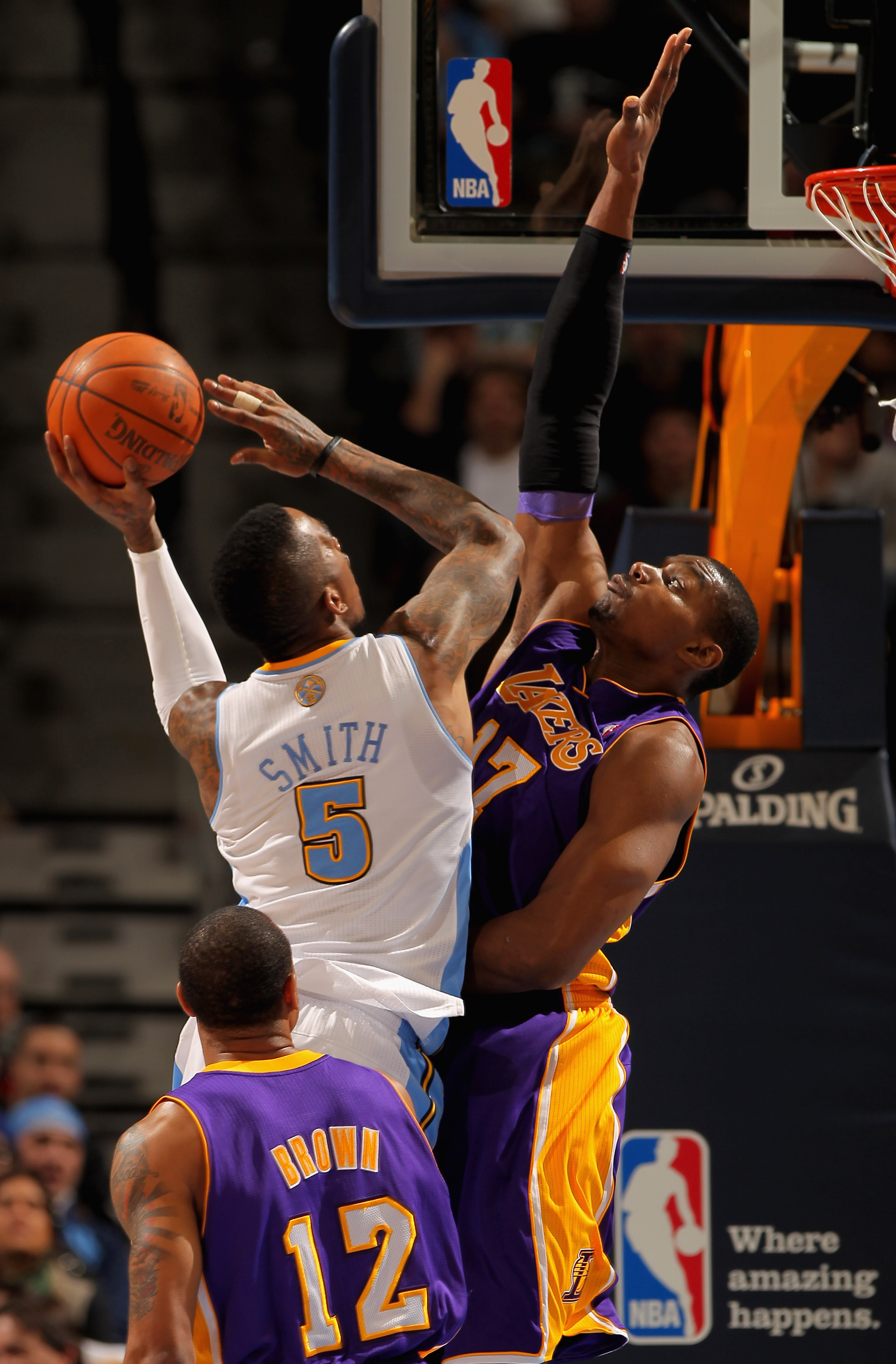 DENVER, CO - JANUARY 21:  J.R. Smith #5 of the Denver Nuggets takes a shot against Andrew Bynum #17 of the Los Angeles Lakers at the Pepsi Center on January 21, 2011 in Denver, Colorado. NOTE TO USER: User expressly acknowledges and agrees that, by downlo