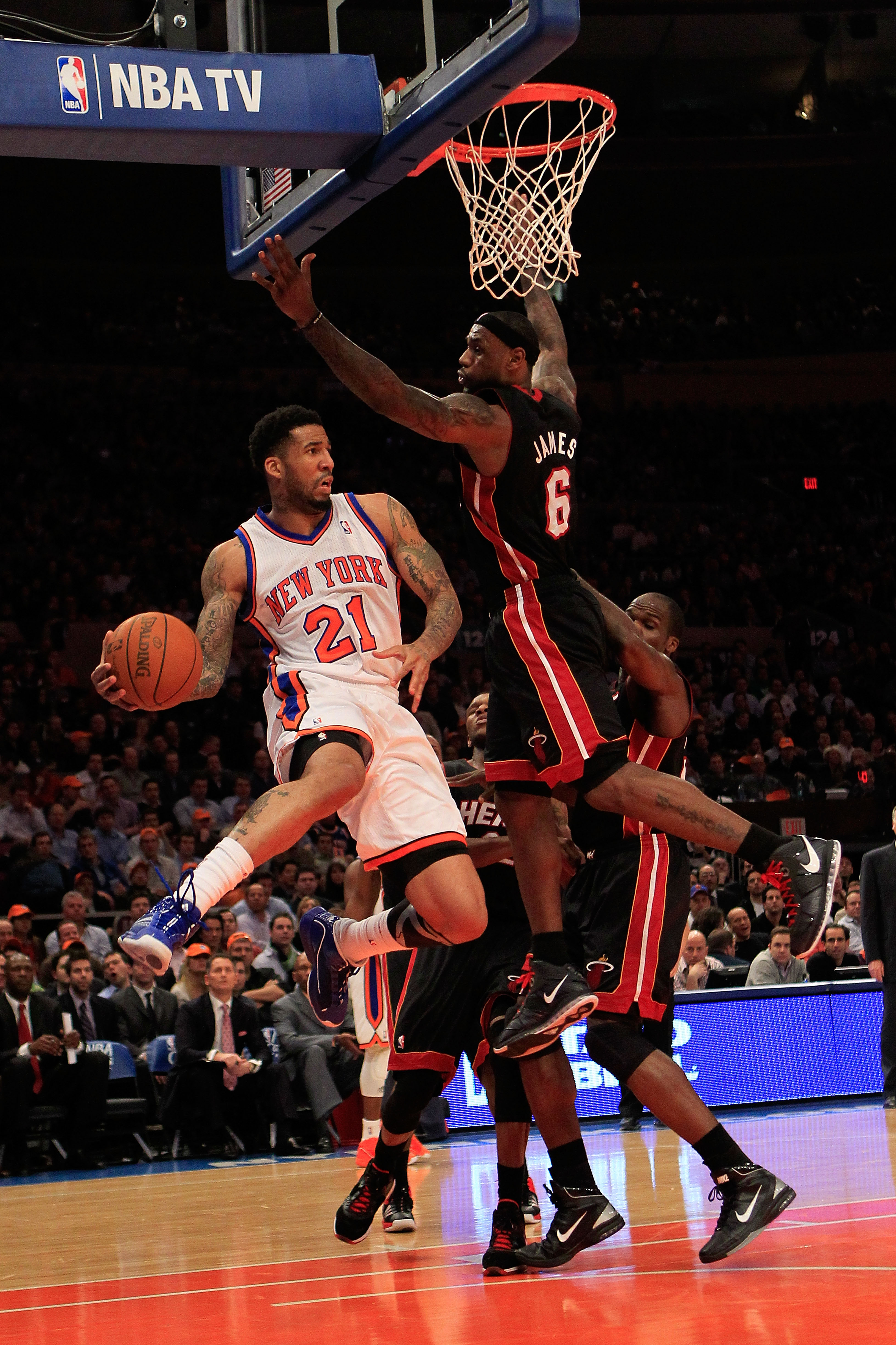 NEW YORK, NY - JANUARY 27: Wilson Chandler #21 of the New York Knicks passes around LeBron James #6 of the Miami Heat at Madison Square Garden on January 27, 2011 in New York City. NOTE TO USER: User expressly acknowledges and agrees that, by downloading