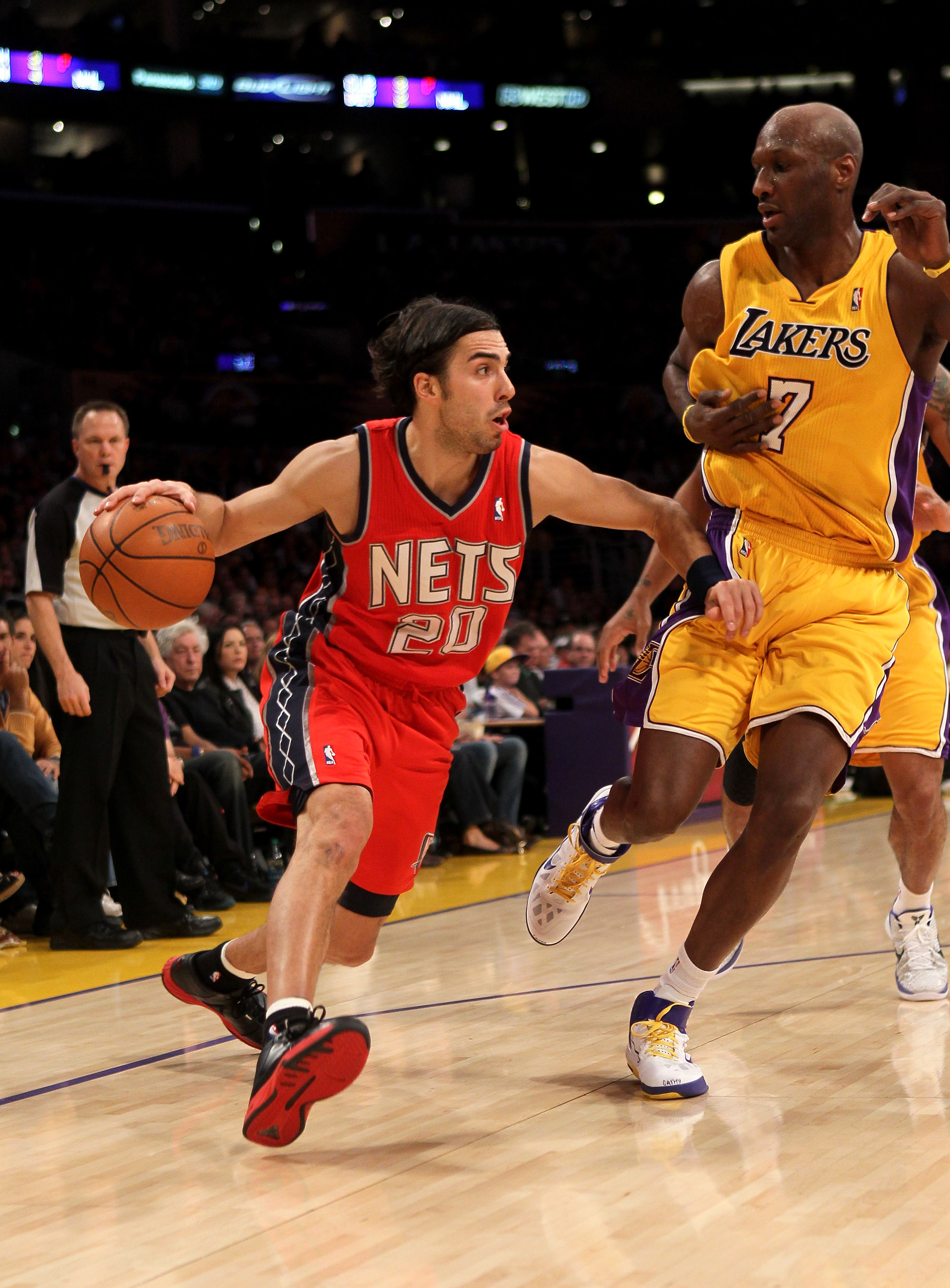LOS ANGELES, CA - JANUARY 14:  Sasha Vujacic #20 of the New Jersey Nets drives against Lamar Odom #7 of the Los Angeles Lakers at Staples Center on January 14, 2011 in Los Angeles, California. The Lakers won 100-88.  NOTE TO USER: User expressly acknowled