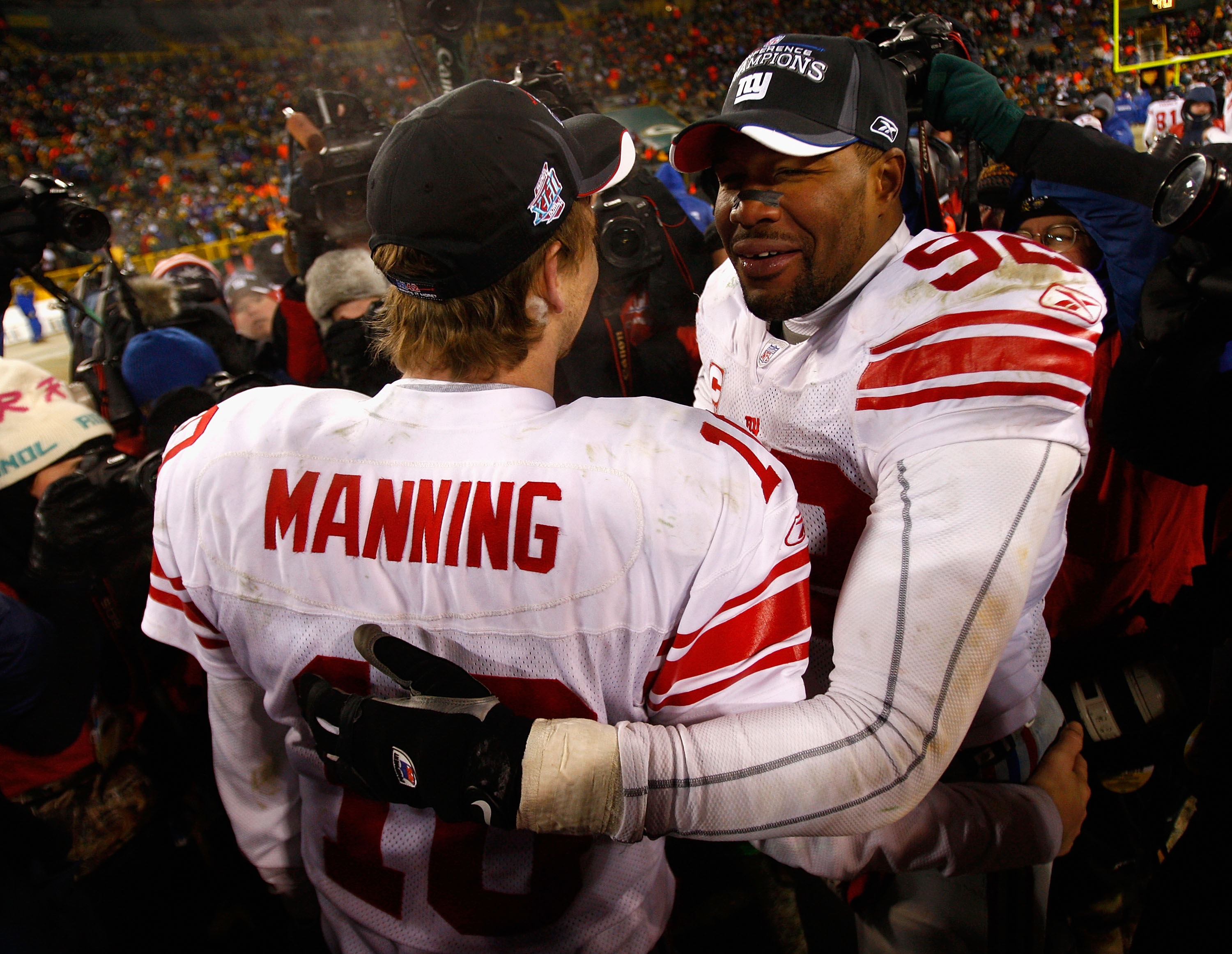 GREEN BAY, WI - JANUARY 20:  Quarterback Eli Manning #10 of the New York Giants celebrates with Michael Strahan #92 after winning the NFC championship game against the Green Bay Packers on January 20, 2008 at Lambeau Field in Green Bay, Wisconsin.   The G