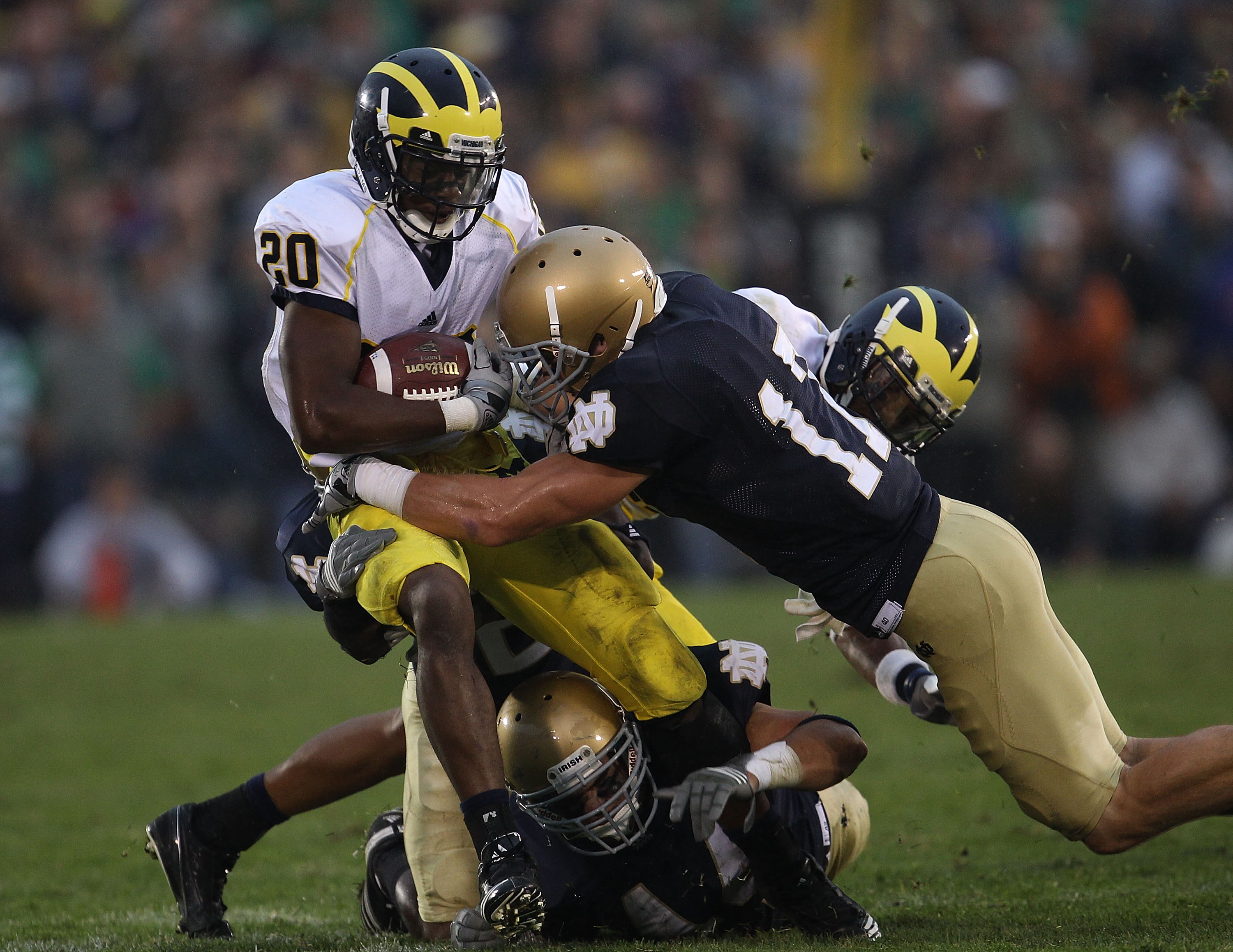 SOUTH BEND, IN - SEPTEMBER 11: Michael Shaw #20 of the Michigan Wolverines is tackled by Carlo Calabrese #44 and Zeke Motta #17 of the Notre Dame Fighting Irish at Notre Dame Stadium on September 11, 2010 in South Bend, Indiana. Michigan defeated Notre Da