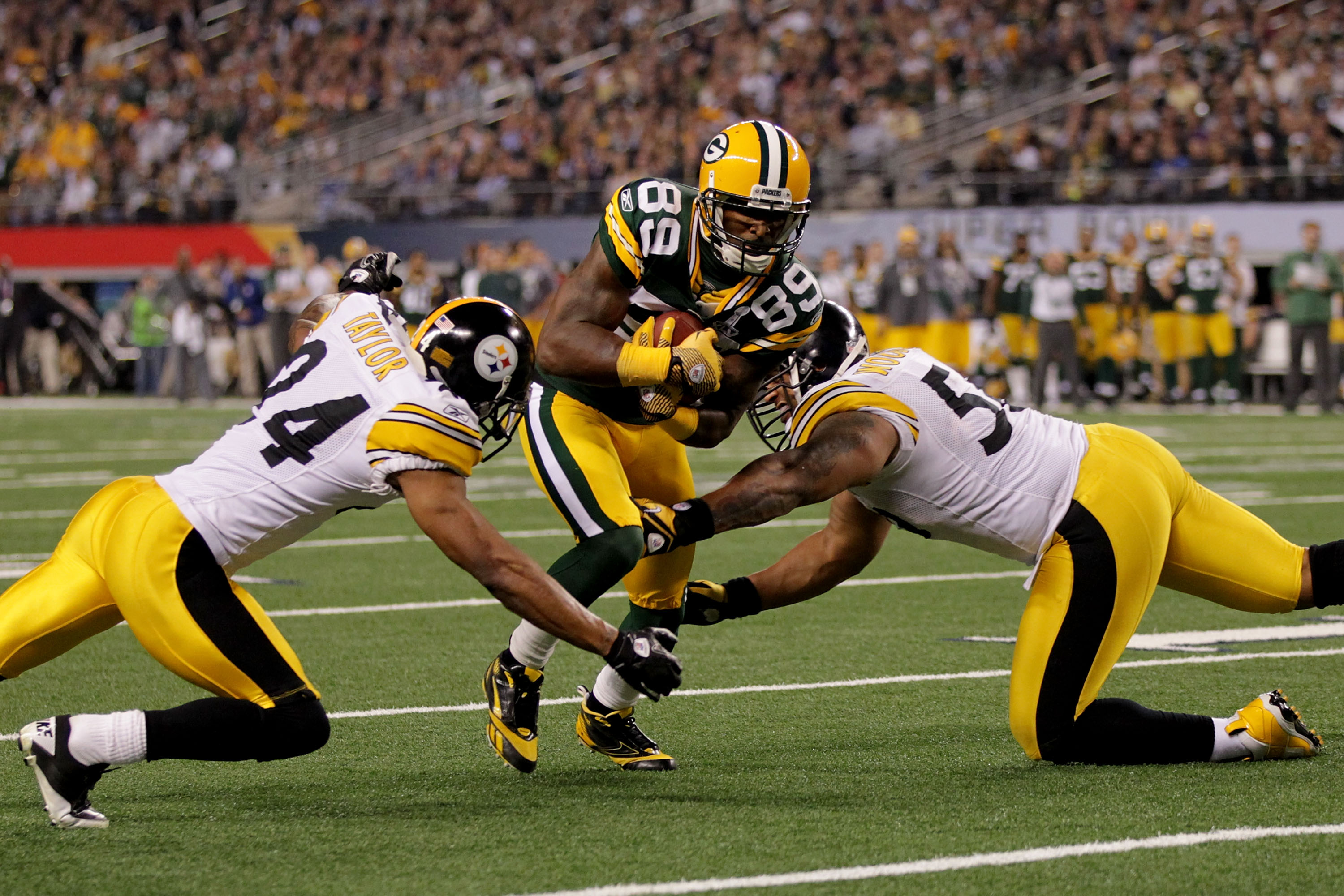 ARLINGTON, TX - FEBRUARY 06:  James Jones #89 of the Green Bay Packers tries to avoid the tackle of LaMarr Woodley #56 and Ike Taylor #24 of the Pittsburgh Steelers and during Super Bowl XLV at Cowboys Stadium on February 6, 2011 in Arlington, Texas.  (Ph
