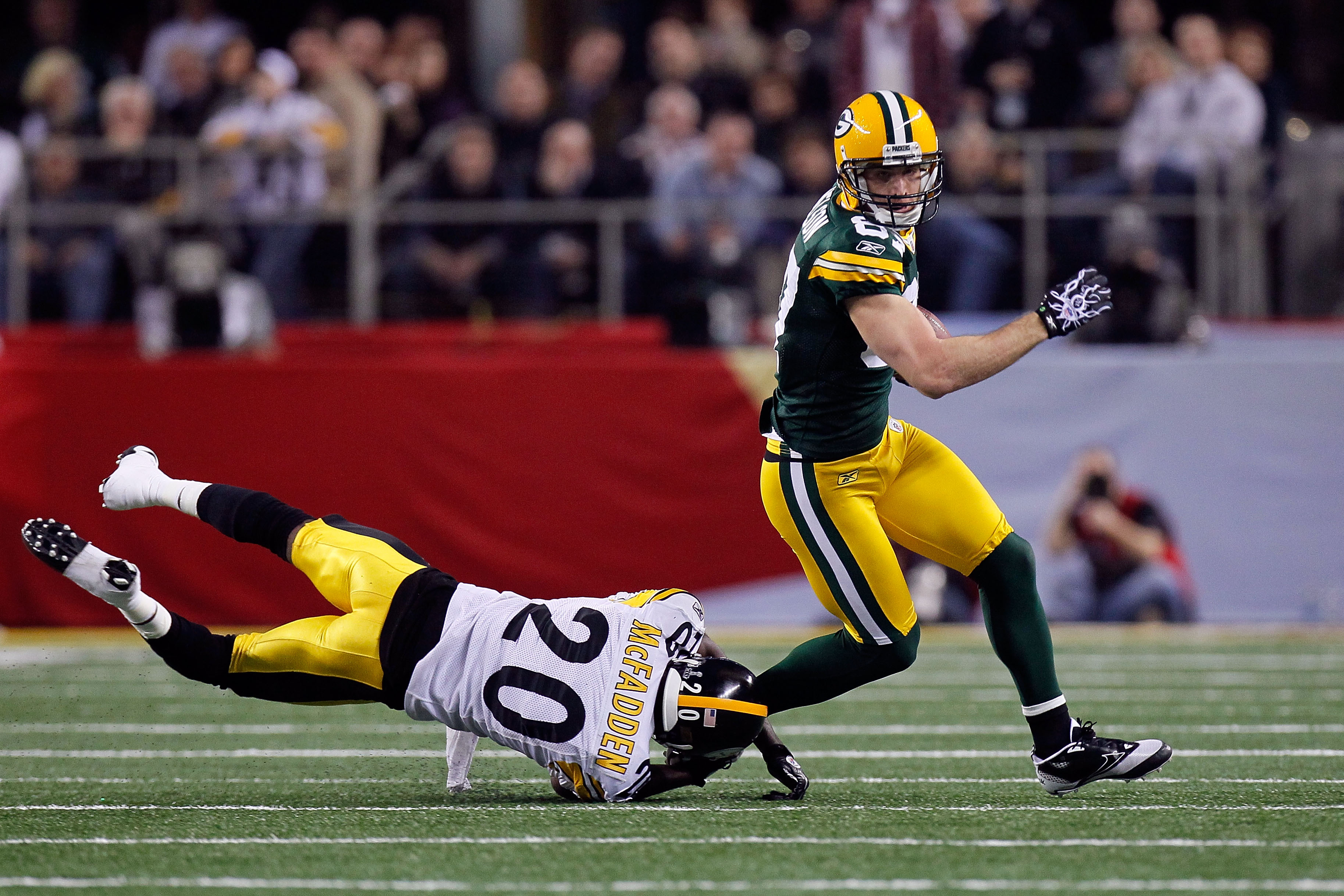 ARLINGTON, TX - FEBRUARY 06: Jordy Nelson #87 of the Green Bay Packers avoids being tackled by Bryant McFadden #20 of the Pittsburgh Steelers during Super Bowl XLV at Cowboys Stadium on February 6, 2011 in Arlington, Texas.  (Photo by Kevin C. Cox/Getty I