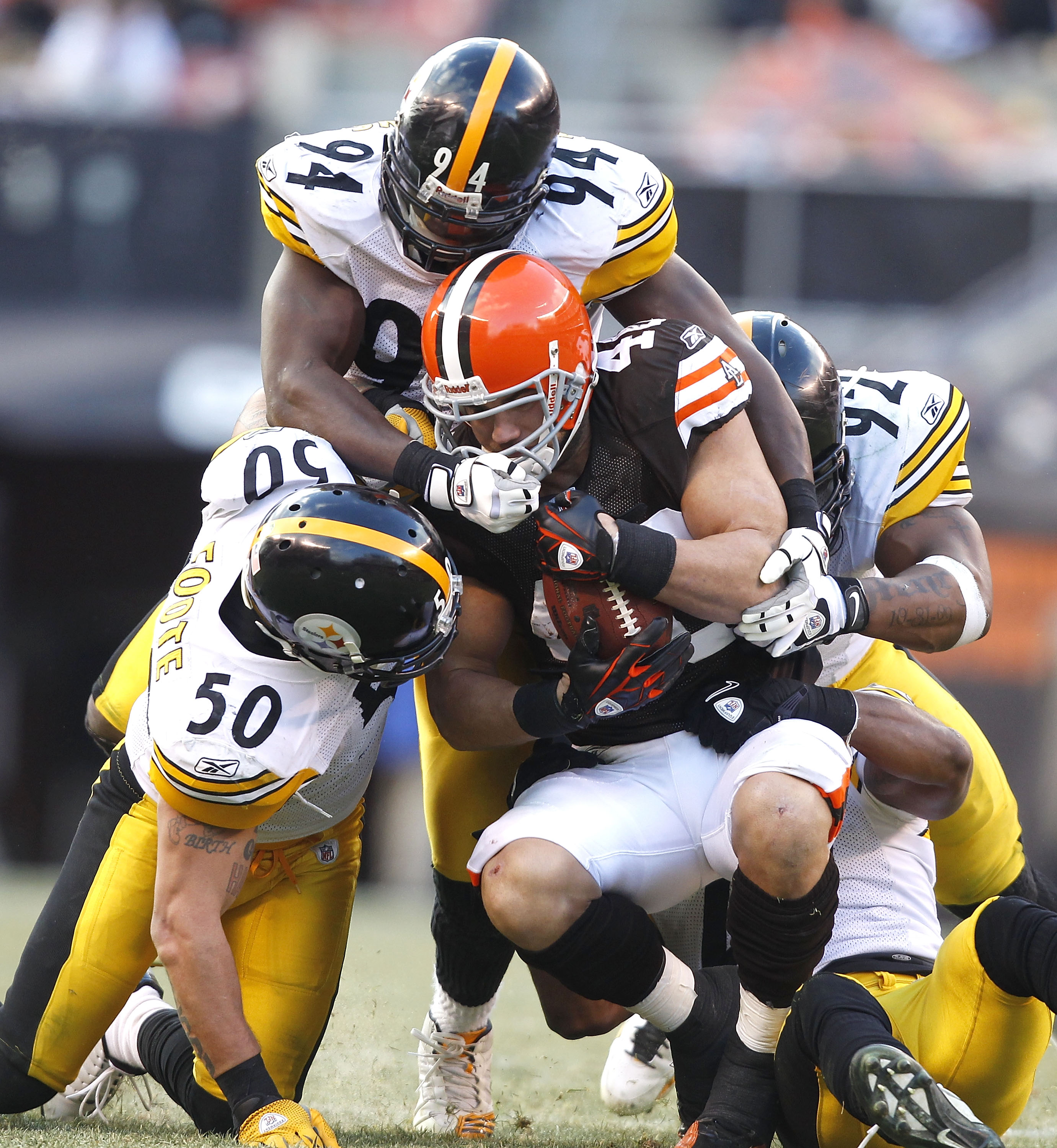 CLEVELAND, OH - JANUARY 02:  Defenders Larry Foote #50, Lawrence Timmons #94 and James Harrison #92 of the Pittsburgh Steelers tackle tailback Peyton Hillis #40 of the Cleveland Browns at Cleveland Browns Stadium on January 2, 2011 in Cleveland, Ohio.  (P