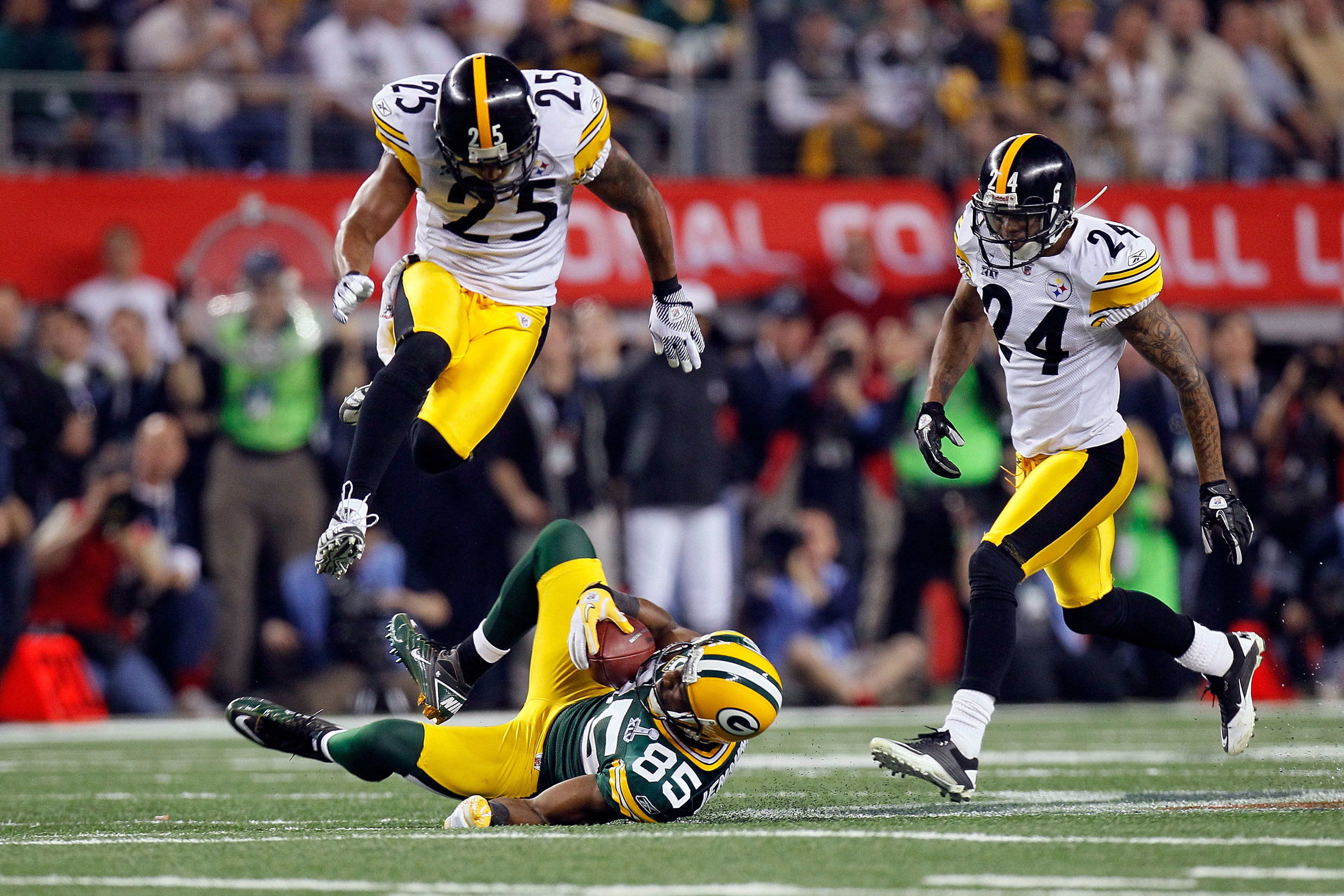 ARLINGTON, TX - FEBRUARY 06:  Greg Jennings #85 of the Green Bay Packers catches a 31 yard pass in the fourth quarter against Ryan Clark #25 and Ike Taylor #24 of the Pittsburgh Steelers during Super Bowl XLV at Cowboys Stadium on February 6, 2011 in Arli
