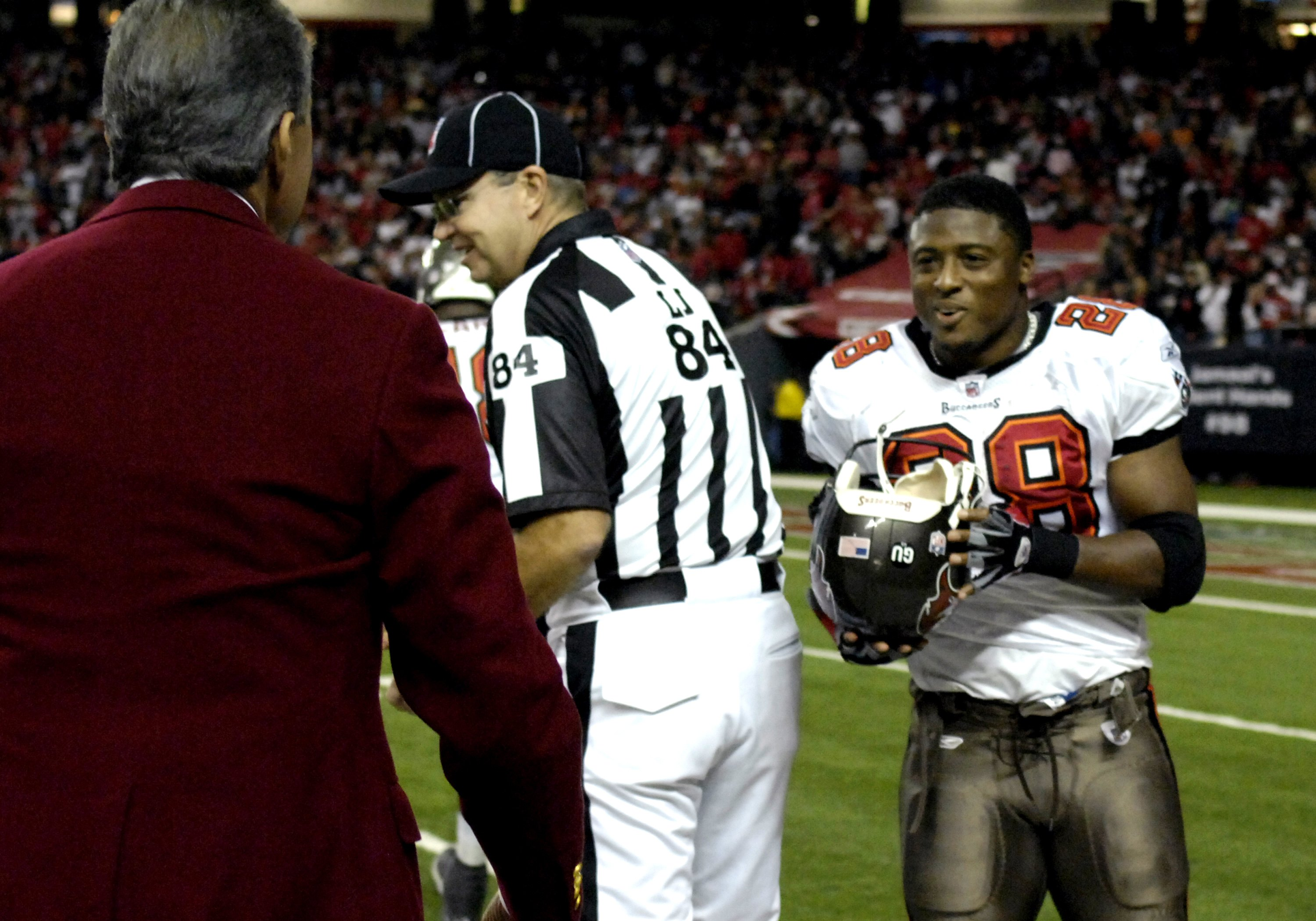 ATLANTA - DECEMBER 14: Onwer Arthur Blank (left) returns the helmet of running back Warrick Dunn #28 of the Tampa Bay Buccaneers at the Georgia Dome on December 14, 2008 in Atlanta, Georgia. Dunn lost his helmet during a tackle on the sidelines near Blank