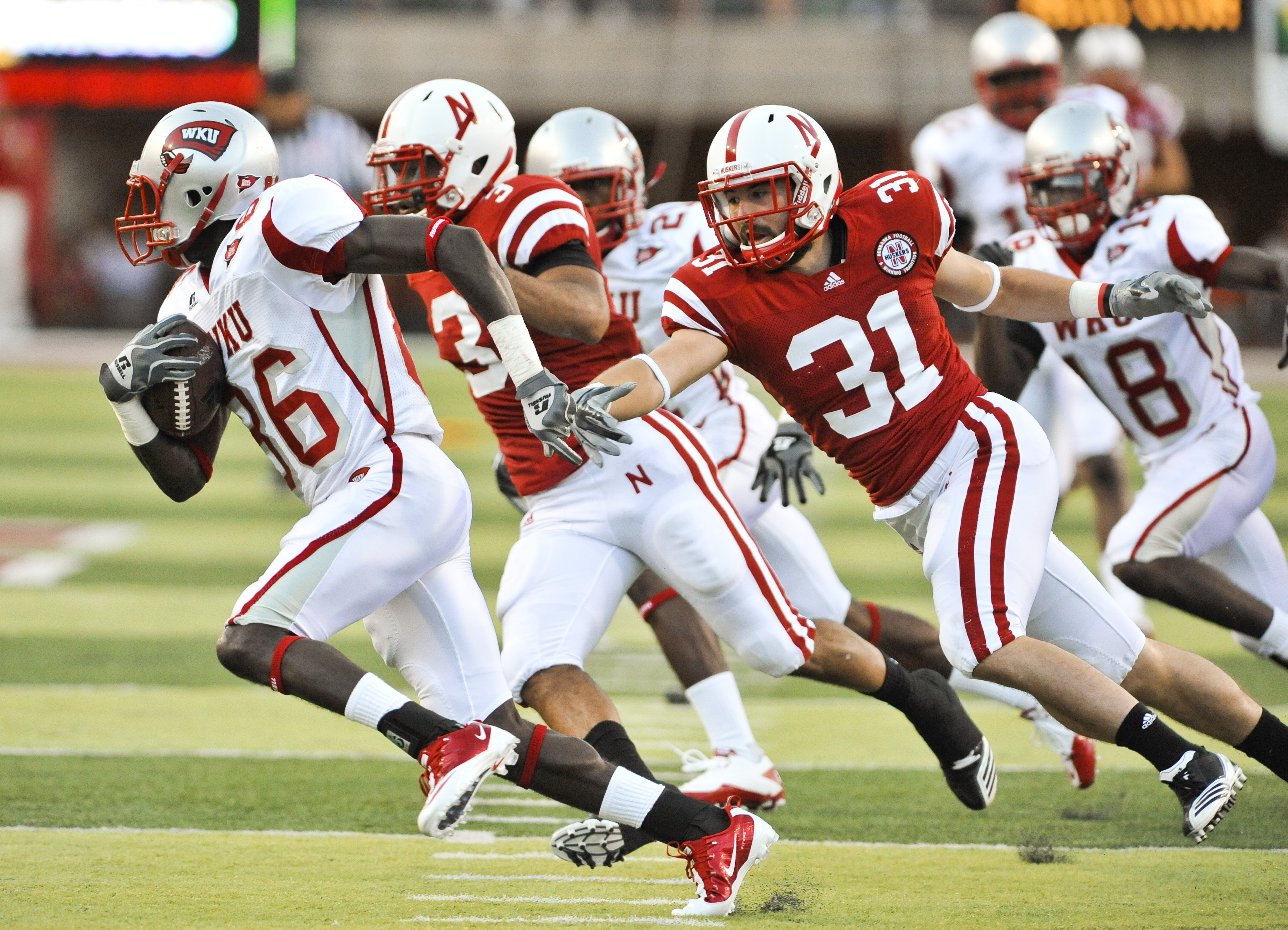 LINCOLN, NE - SEPTEMBER 04: Willie McNeal of the Western Kentucky Hilltoppers attempts to out run Jase Dean #31 of the Nebraska Cornhuskers after a mishandled punt during first half action of their game at Memorial Stadium on September 4, 2010 in Lincoln,