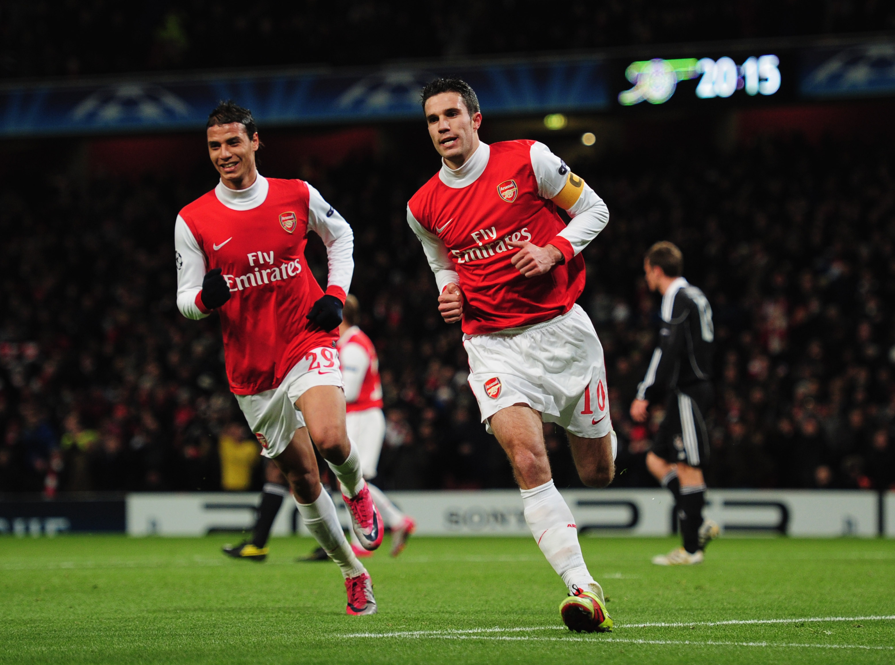 LONDON, ENGLAND - DECEMBER 08:  Robin van Persie of Arsenal celebrates with Marouane Chamakh (L) as he scores their first goal from the penalty spot during the UEFA Champions League Group H match between Arsenal and FK Partizan Belgrade at the Emirates St