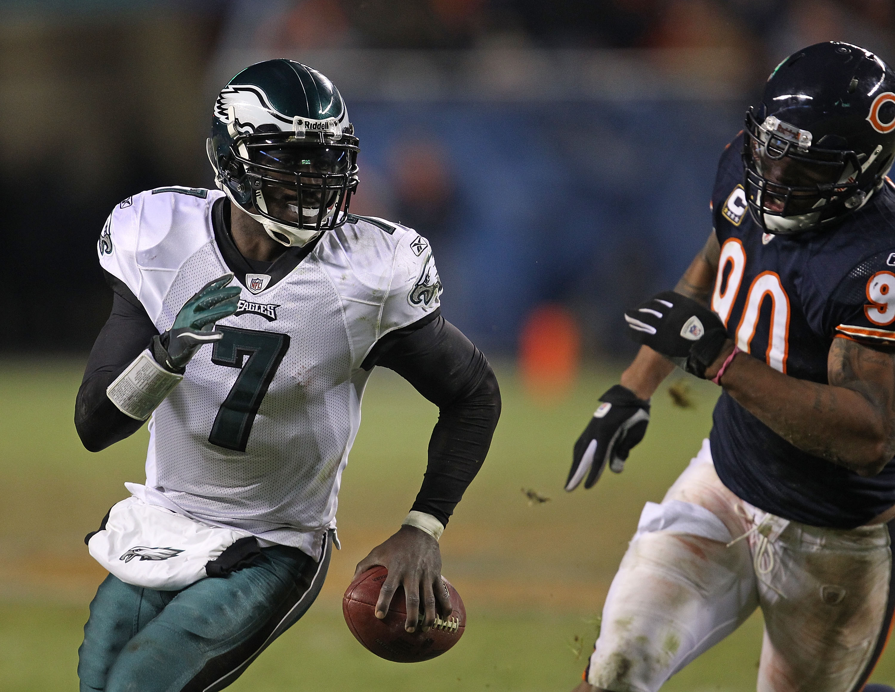 CHICAGO - NOVEMBER 28: Michael Vick #7 of the Philadelphia Eagles runs to avoid Julius Peppers #90 of the Chicago Bears at Soldier Field on November 28, 2010 in Chicago, Illinois. The Bears defeated the Eagles 31-26. (Photo by Jonathan Daniel/Getty Images