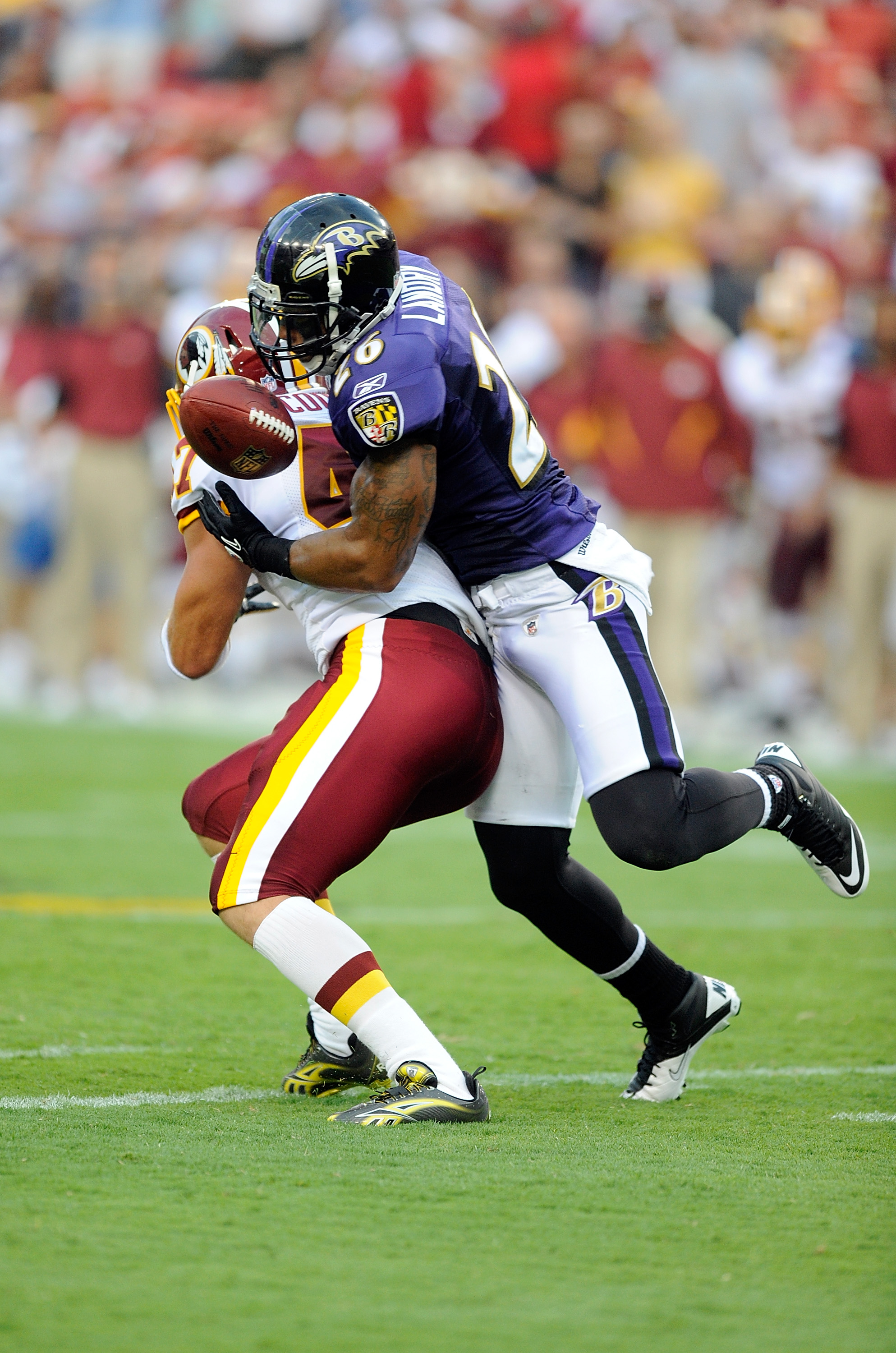 LANDOVER, MD - AUGUST 21:  Dawan Landry #26 of the Baltimore Ravens breaks up a pass during the preseason game intended for Chris Cooley #47 of the Washington Redskins at FedExField on August 21, 2010 in Landover, Maryland.  (Photo by Greg Fiume/Getty Ima