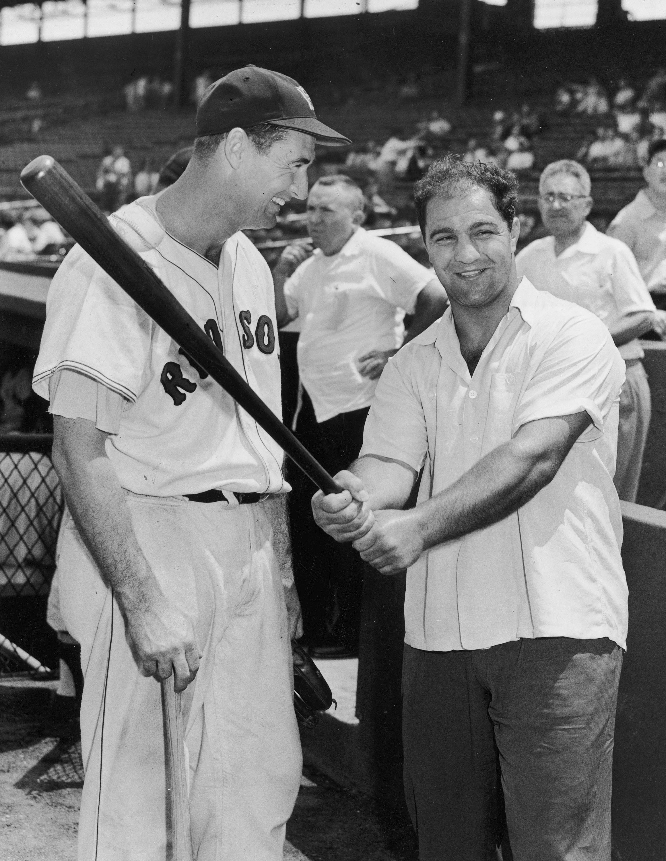 BOSTON - CIRCA 1955:  (UNDATED FILE PHOTO) Baseball legend Ted Williams (1918 - 2002) of the Boston Red Sox (L) laughs as American boxing great Rocky Marciano (1923 - 1969) swings a bat circa 1955. The 83-year-old Williams, who was the last major league p