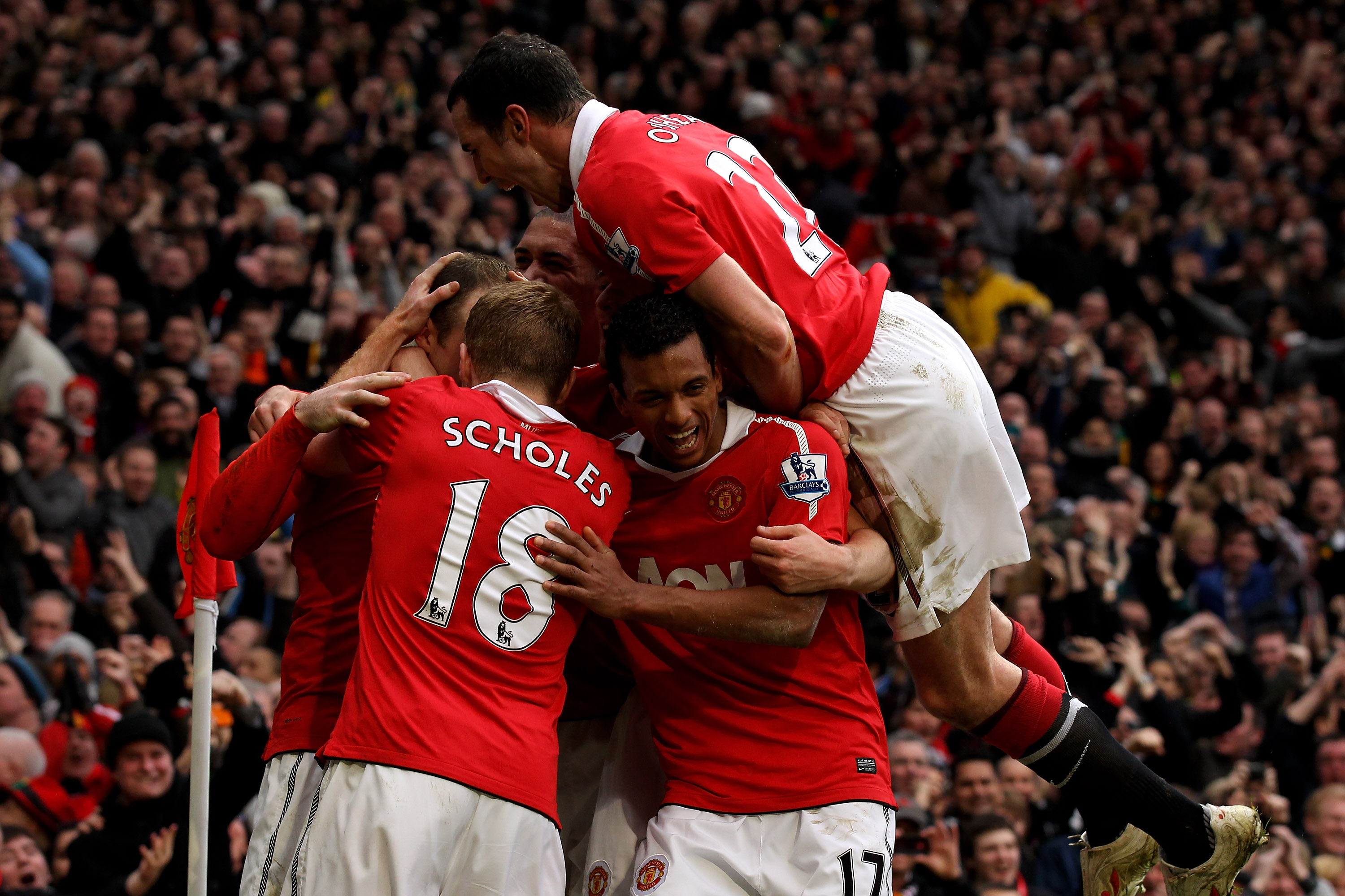 MANCHESTER, ENGLAND - FEBRUARY 12:  Wayne Rooney of Manchester United is mobbed by teammates after scoring during the Barclays Premier League match between Manchester United and Manchester City at Old Trafford on February 12, 2011 in Manchester, England.