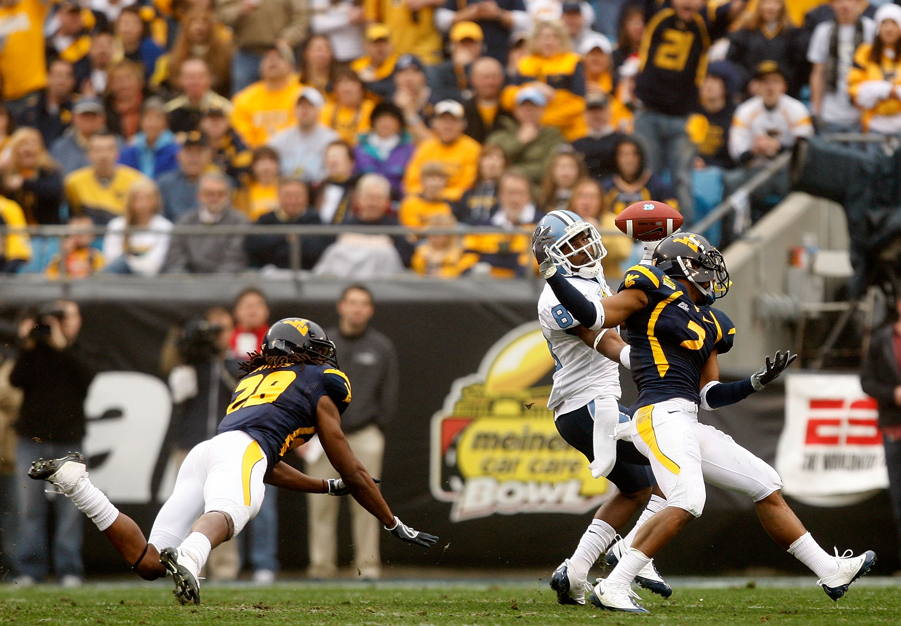 CHARLOTTE, NC - DECEMBER 27:  Hakeem Nicks #88 of the North Carolina Tar Heels catches a touchdown over Ellis Lankster #2 and teammate Robert Sands #28 of the West Virginia Mountaineers during the Meineke Car Care Bowl on December 27, 2008 at Bank of Amer