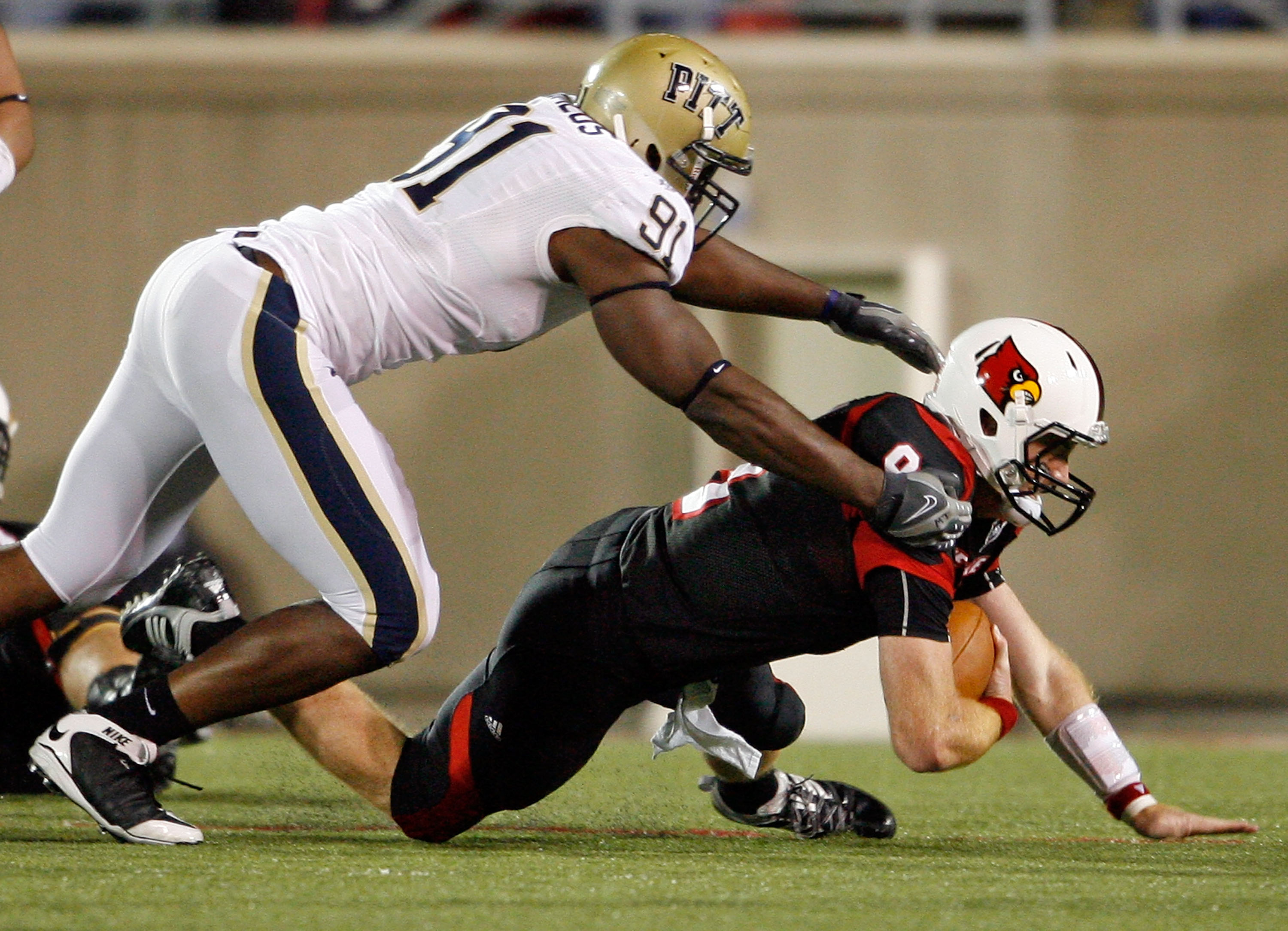 LOUISVILLE, KY - OCTOBER 02:  Adam Froman #9 of the Louisville Cardinals is sacked by Greg Romeus #91  of the Pittsburgh Panthers during the Big East Conference game at Papa John's Cardinal Stadium on October 2, 2009 in Louisville, Kentucky.  (Photo by An