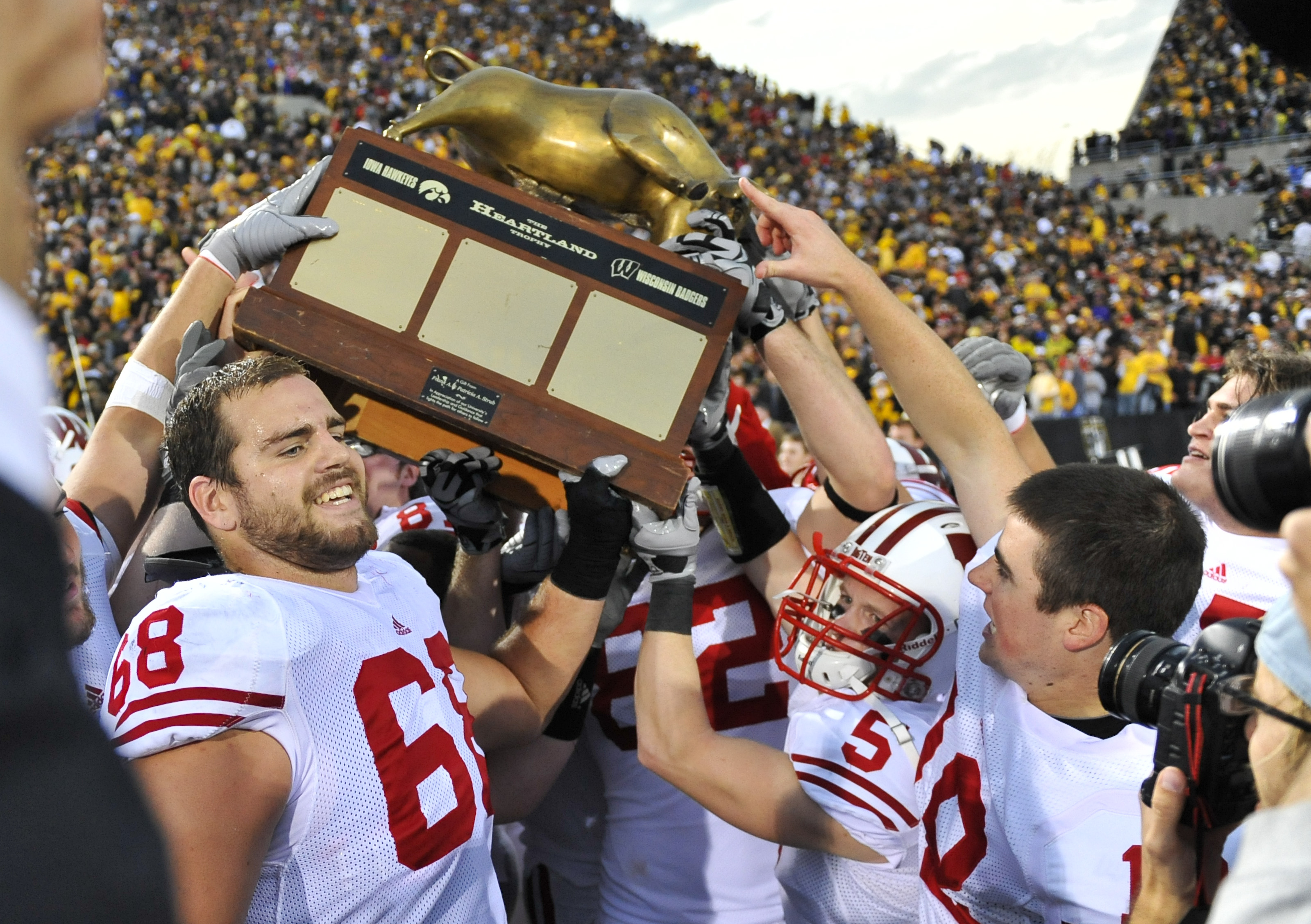 IOWA CITY, IA - OCTOBER 23: Offensive lineman Gabe Carimi #68 of the Wisconsin Badgers holds the Heartland Trophy with his teammates as they celebrate their victory of the University of Iowa Hawkeyes at Kinnick Stadium on October 23, 2010 in Iowa City, Io