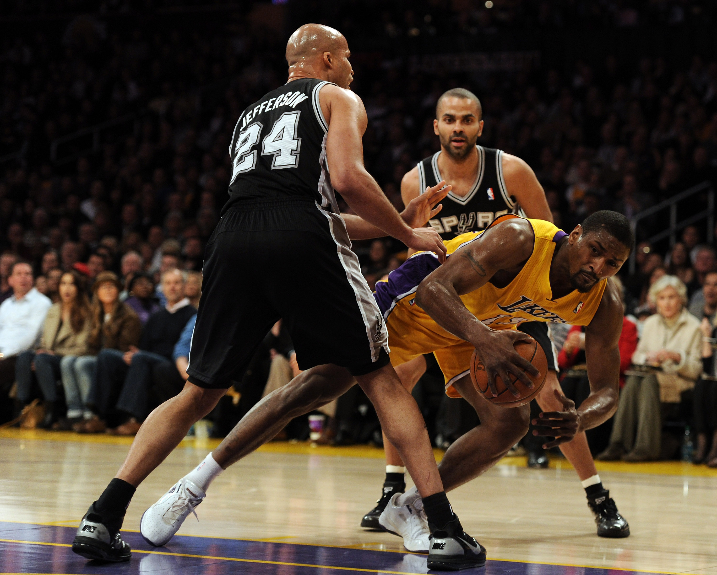 LOS ANGELES, CA - FEBRUARY 03:  Ron Artest #15 of the Los Angeles Lakers loses his footing as he is guarded by Richard Jefferson #24 and Tony Parker #9 of the San Antonio Spurs at Staples Center on February 3, 2011 in Los Angeles, California.  NOTE TO USE