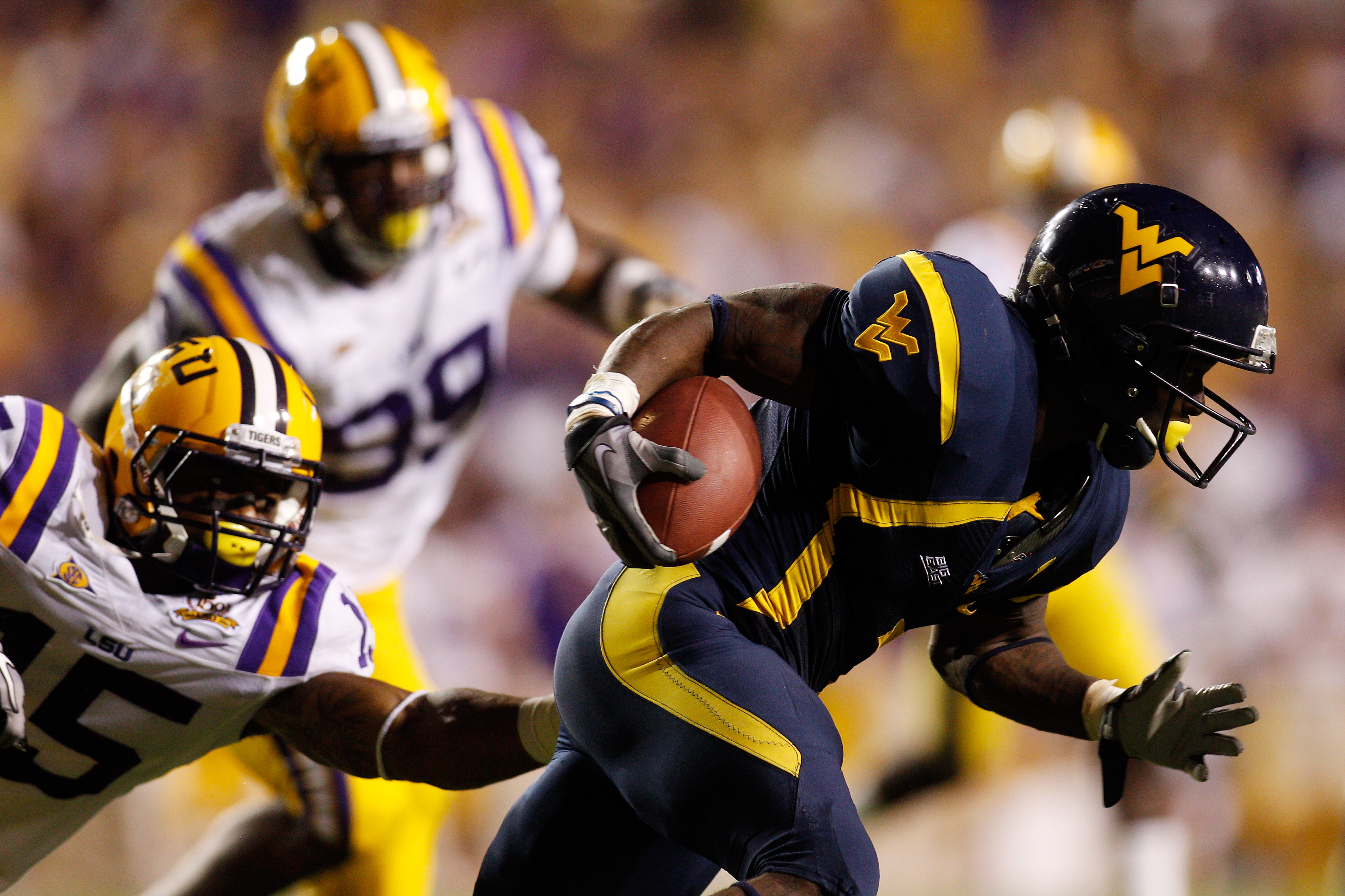 BATON ROUGE, LA - SEPTEMBER 25:  Noel Devine #7 of the West Virginia Mountaineers avoids a tackle by Brandon Taylor #15 of the Louisiana State Univeristy Tigers at Tiger Stadium on September 25, 2010 in Baton Rouge, Louisiana.  The Tigers defeated the Mou