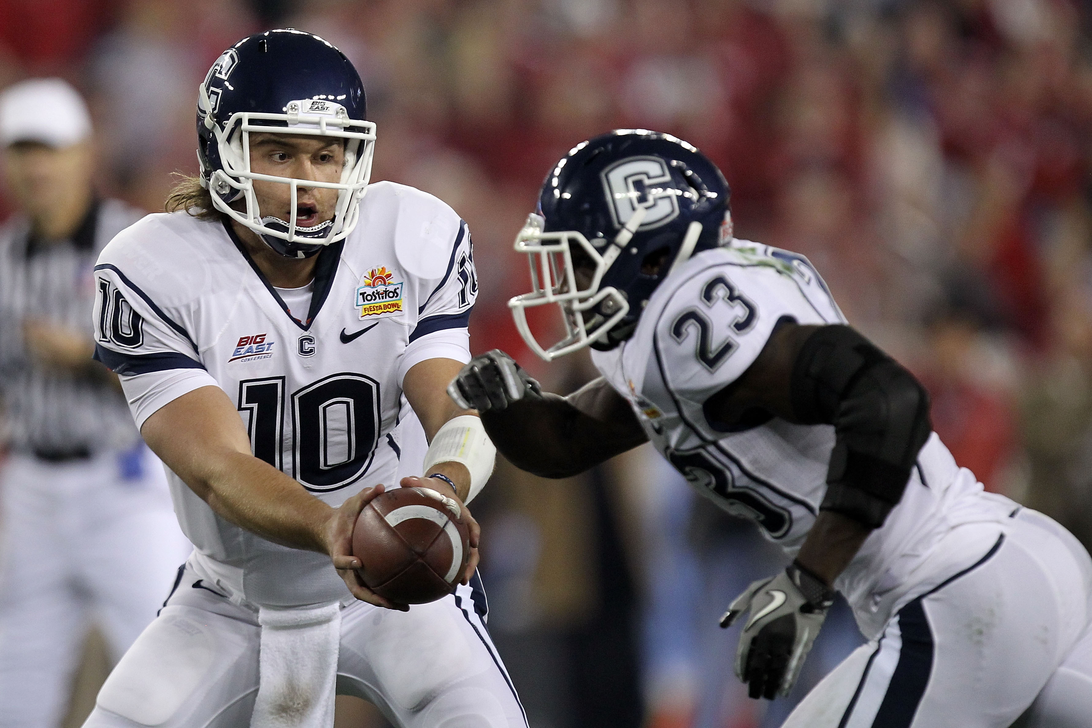 GLENDALE, AZ - JANUARY 01:  Zach Frazer #10 of the Connecticut Huskies  hands the ball off to Jordan Todman #23 against the Oklahoma Sooners during the Tostitos Fiesta Bowl at the Universtity of Phoenix Stadium on January 1, 2011 in Glendale, Arizona.  (P