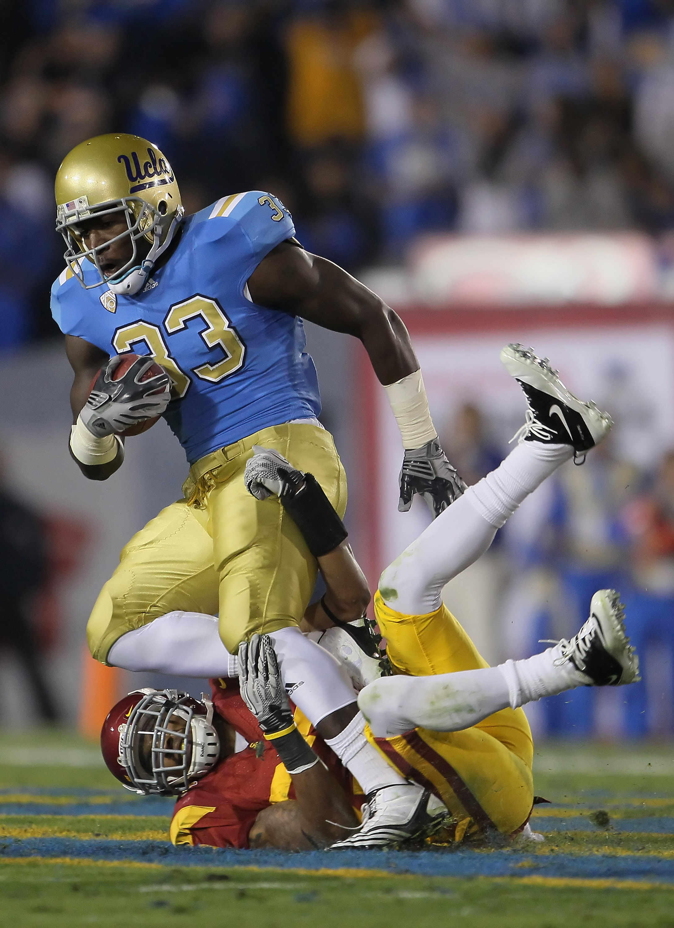 PASADENA, CA - DECEMBER 04:  Running back Derrick Coleman #33 of the UCLA Bruins is brought down by Marshall Jones #27 of the USC Trojans during the first half at the Rose Bowl on December 4, 2010 in Pasadena, California.  (Photo by Jeff Gross/Getty Image